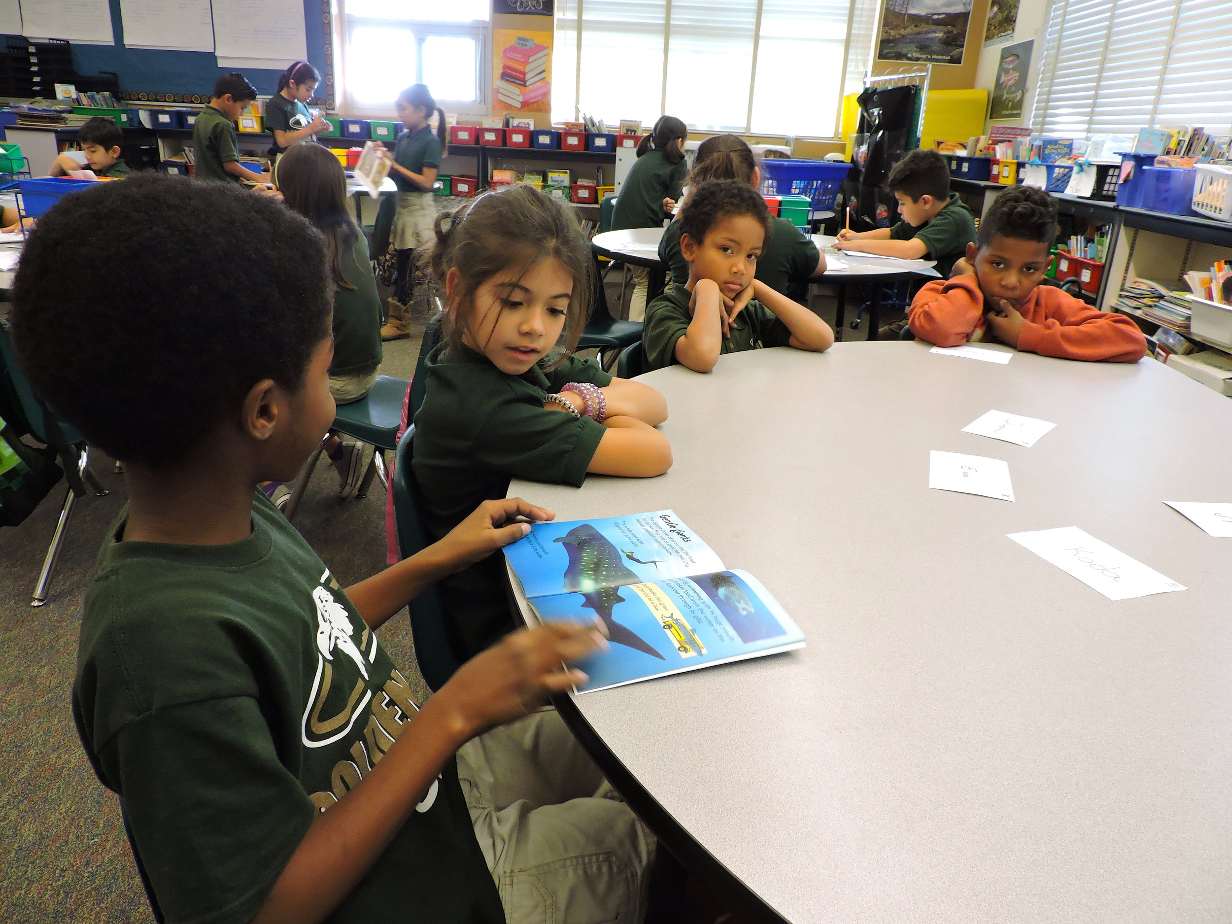 An image of four students in one of our Read Aloud Program sessions looking through a book together.