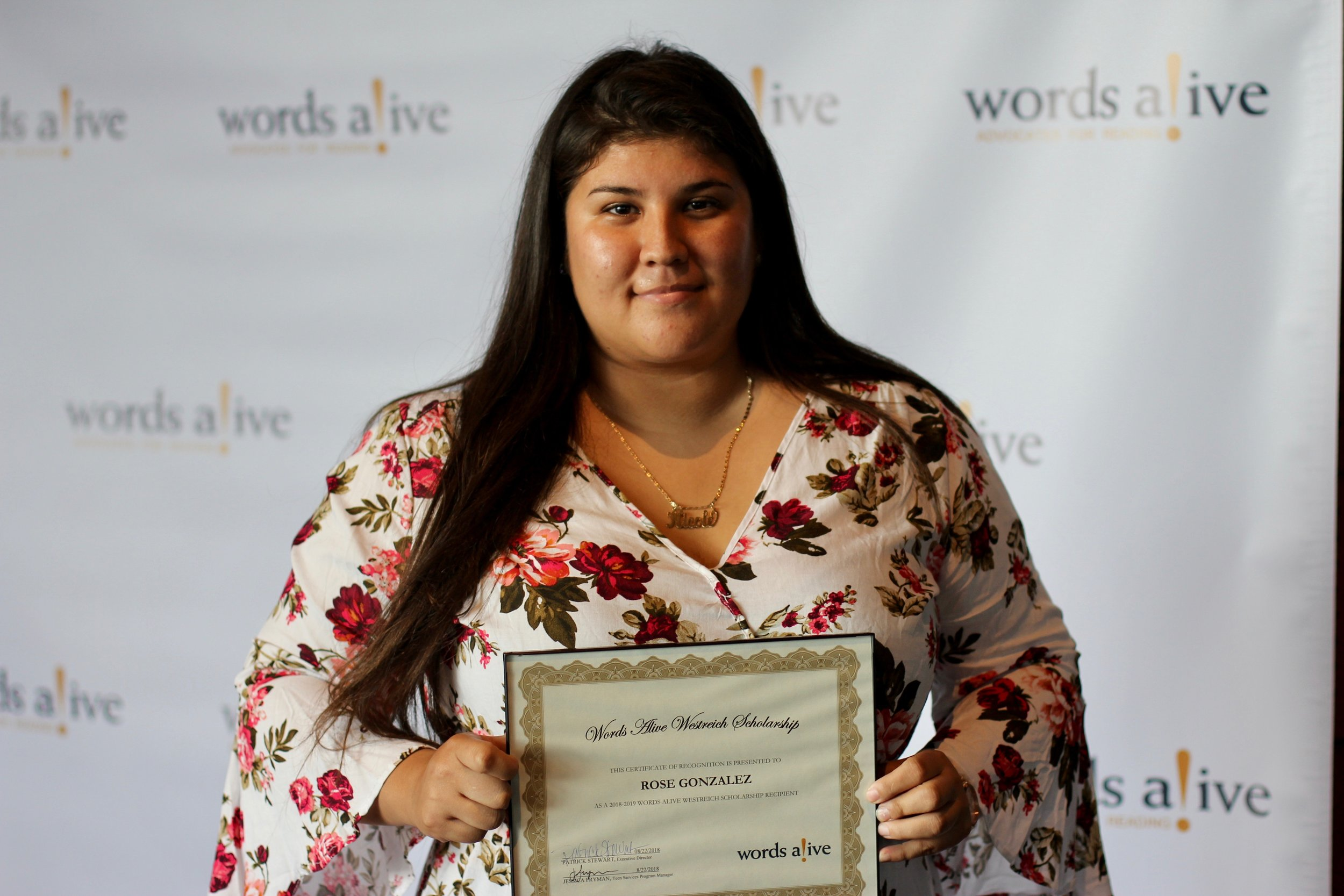 An image of Rose Gonzalez holding her award in front of a Words Alive backdrop.