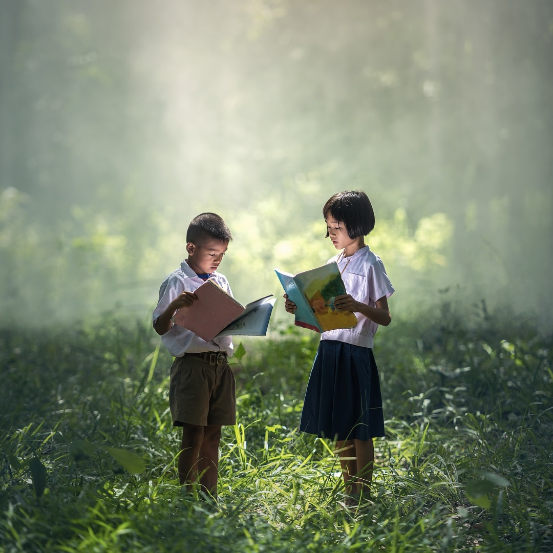An image of two children standing in a green field while reading books.