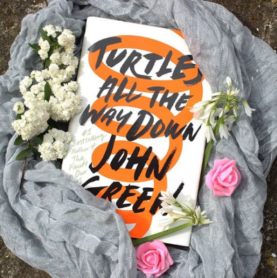 An image of  Turtles All the Way Down  surrounded by flowers! Photo credit:  courtneyandherbooks