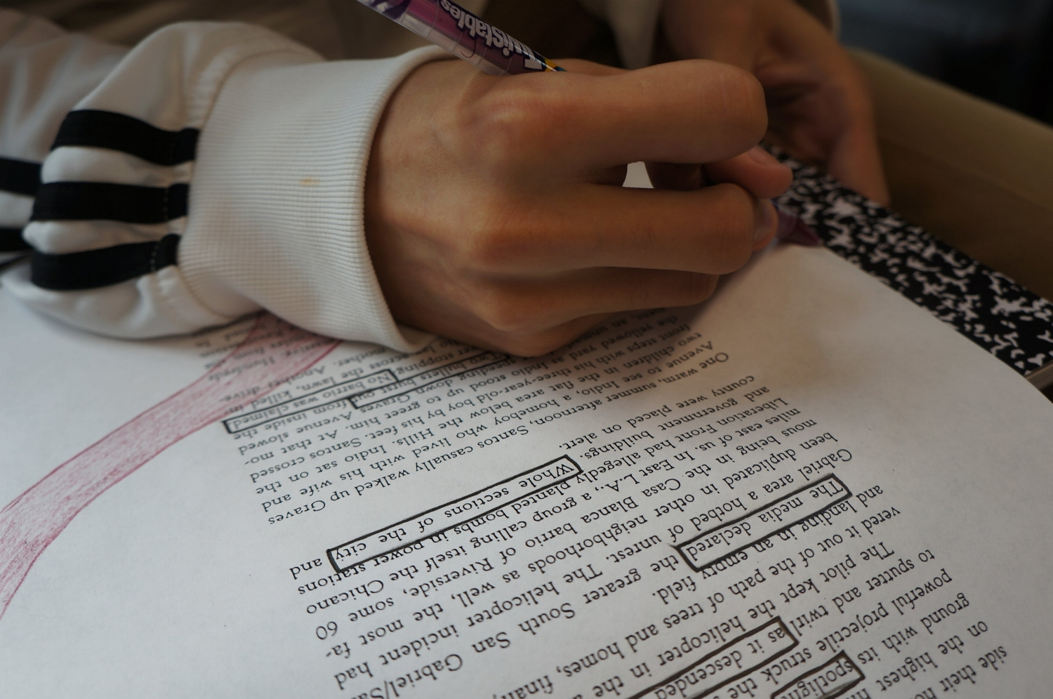 An image of one of our Adolescent Book Group students working on a blackout poetry exercise, which requires them to select certain words and phrases from a page of text to construct a poem.
