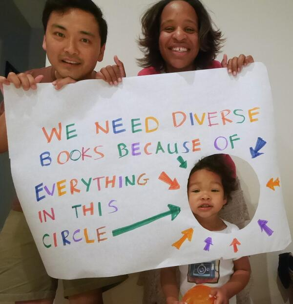 "Image of young adult author Nicola Yoon and her husband holding up a sign that says, ""We need diverse books because of everything in this circle."" There is a circle cut out of the sign and their daughter is standing so her face is in the circle. Photo credit:  Nicola Yoon"