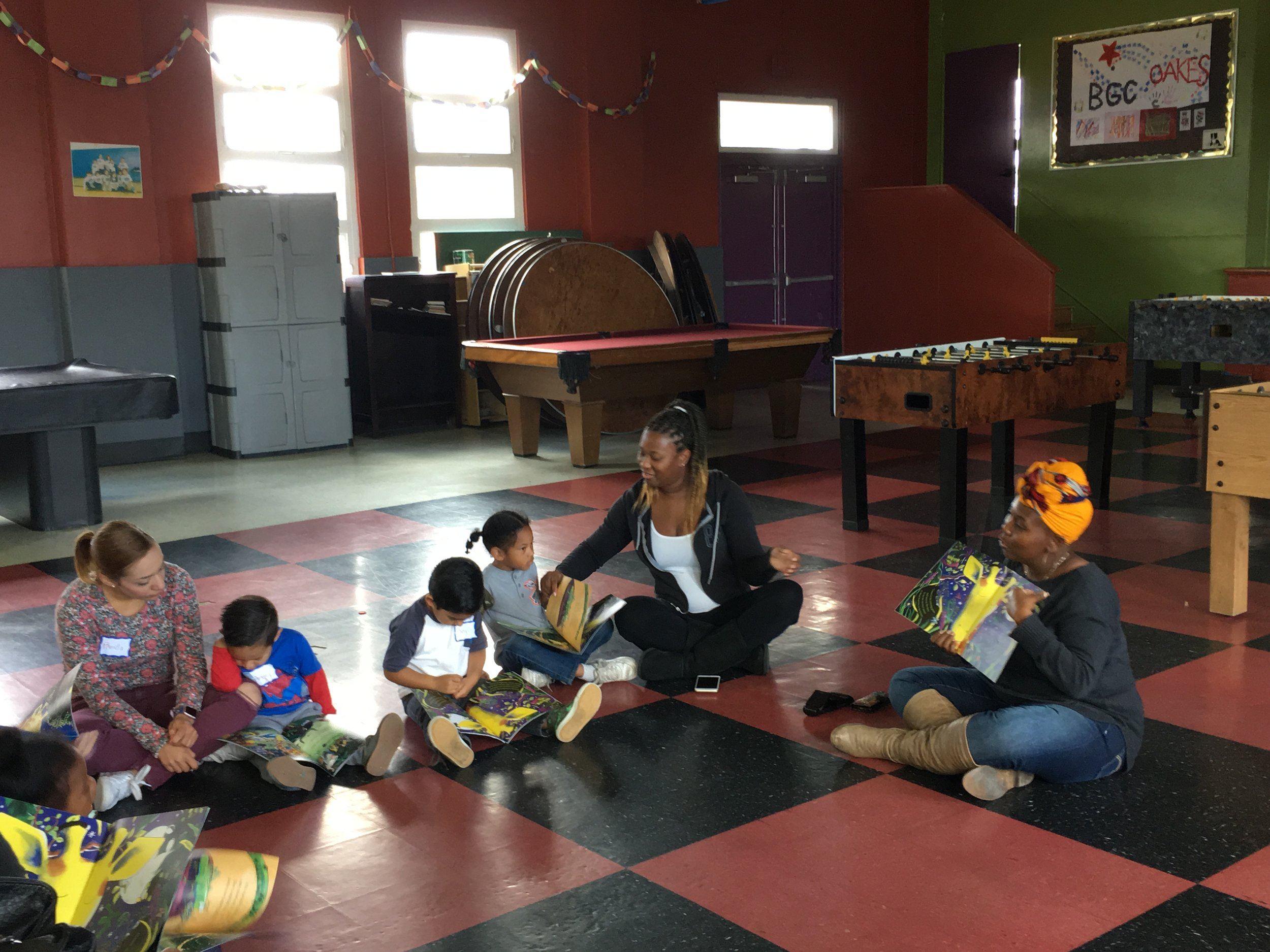 An image of Sheena facilitating a Family Literacy session. She is sitting on the floor with guardians and children while they all look at books together.