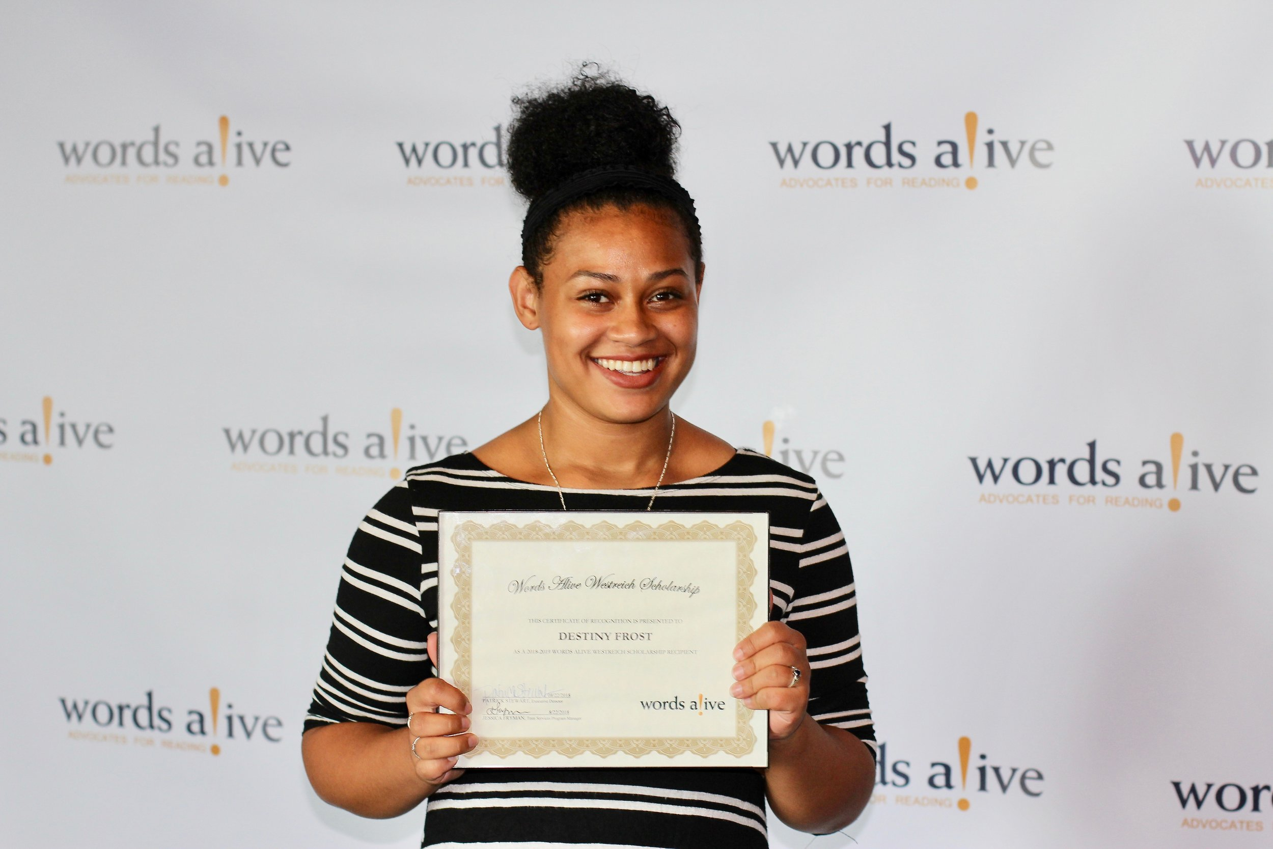 An image of Destiny holding up her award at the 2018 Words Alive Westreich Scholarship Award Ceremony.
