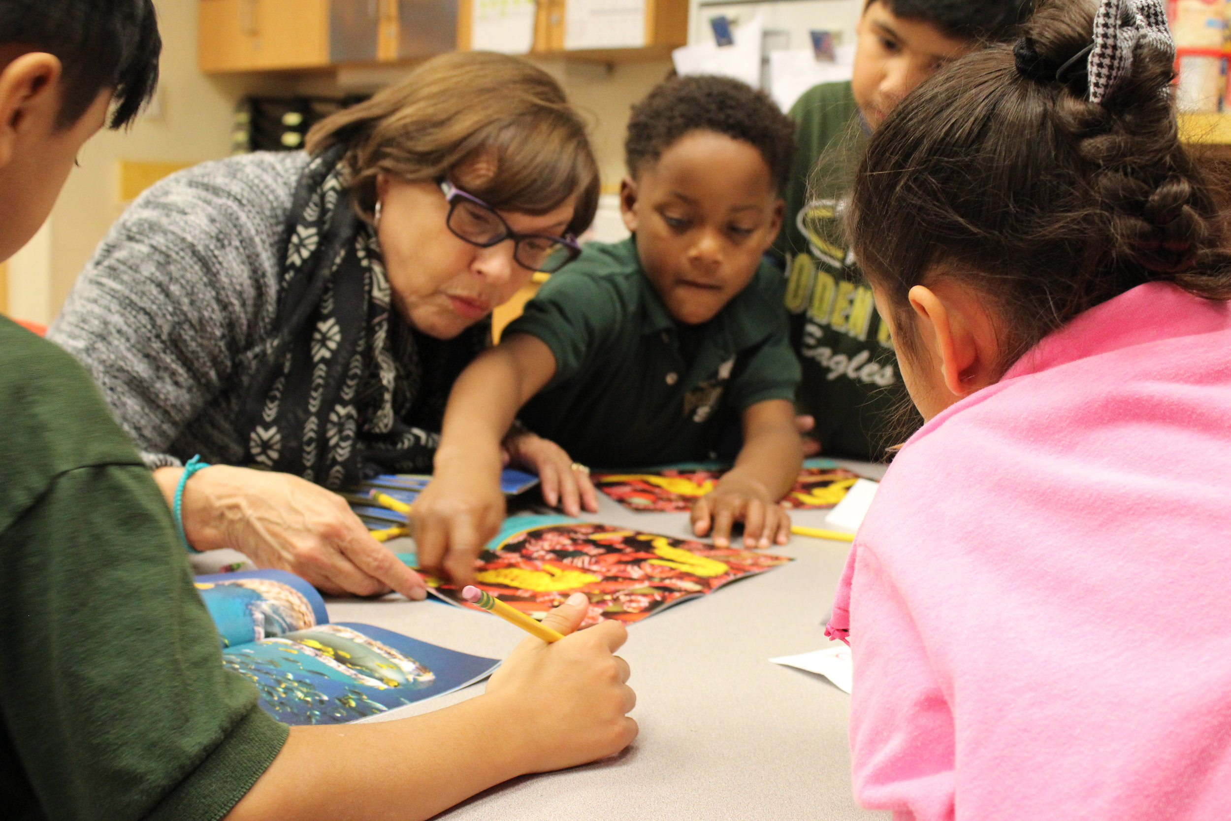 An image of Read Aloud Program students exploring a book together with Words Alive volunteer Sharon Gruby! A $100 donation to our Champions for Youth campaign provides 75 new books for children to take home and build their libraries.