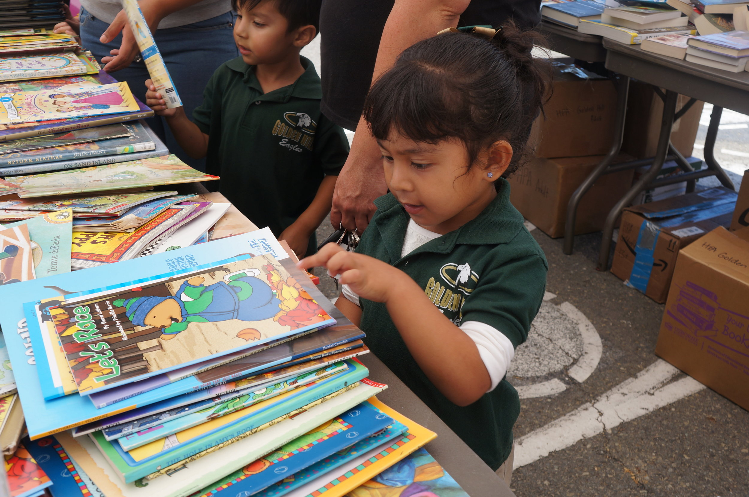 An image of a young student from Golden Hill pointing at a large pile of books at a book giveaway we hosted in 2017.