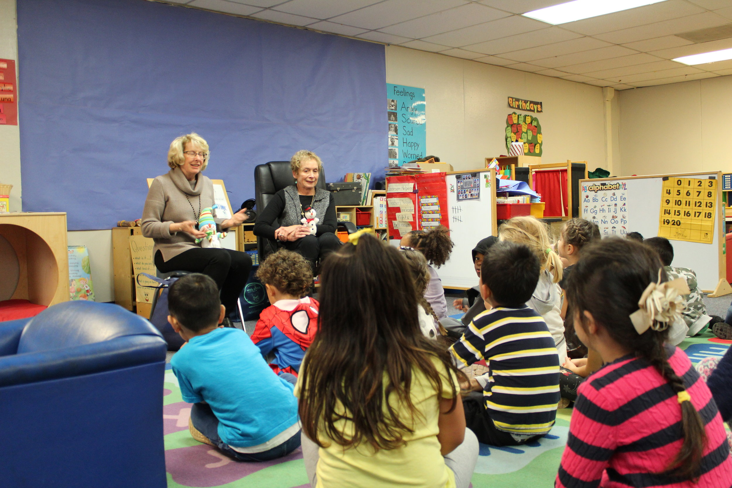 An image of two of our Read Aloud Program volunteers engaging with their preschool classroom.