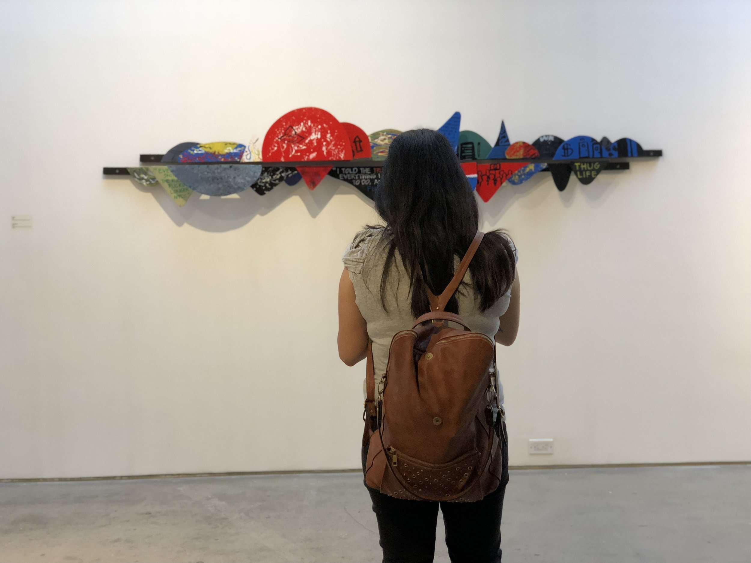 Image of a person with their back turned towards the camera. They are standing in front of one of the sculptures our students made for this year's Art & Literacy Project.