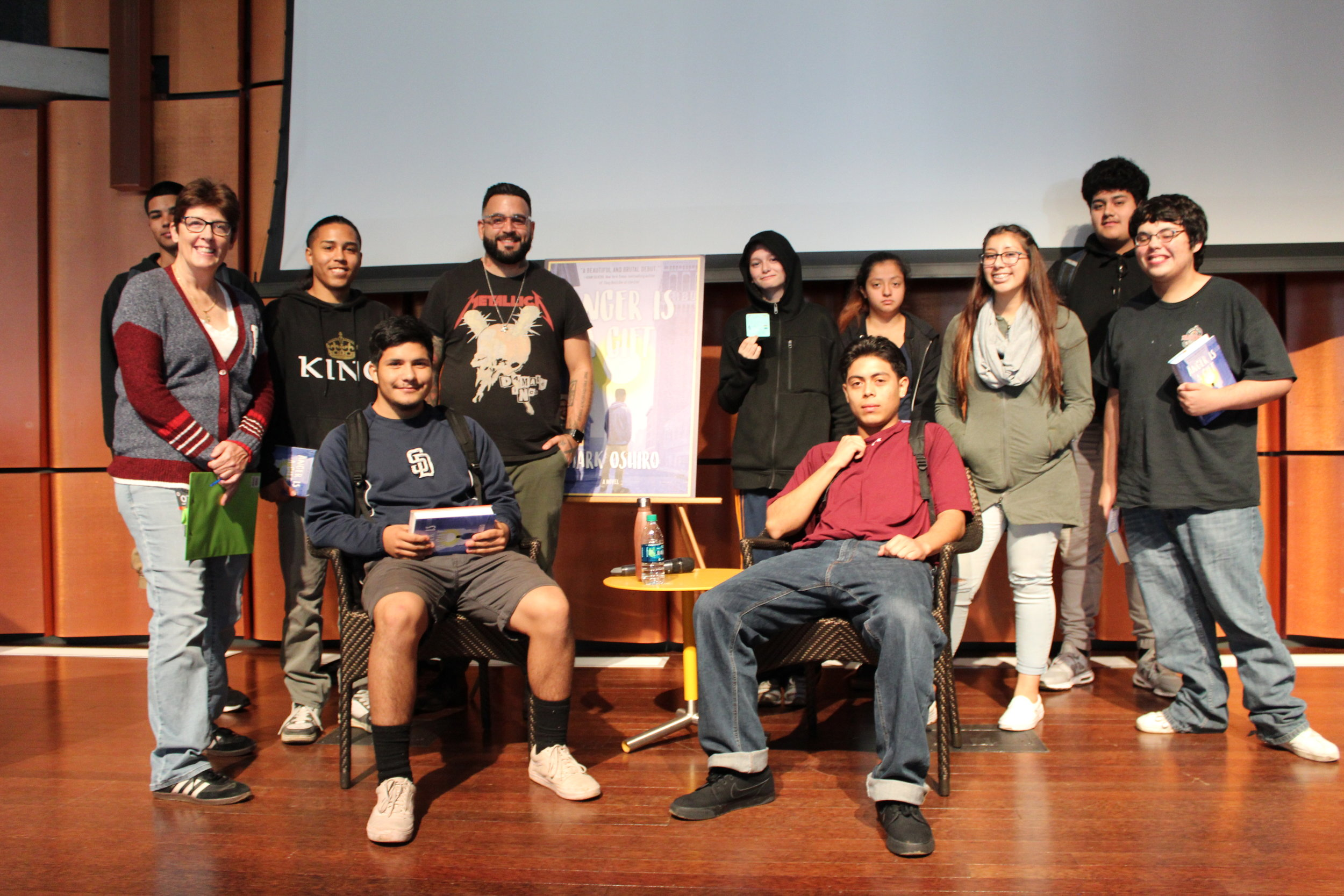 Author Mark Oshiro poses with one of our classes from Monarch School after giving a talk about his book, Anger is a Gift.