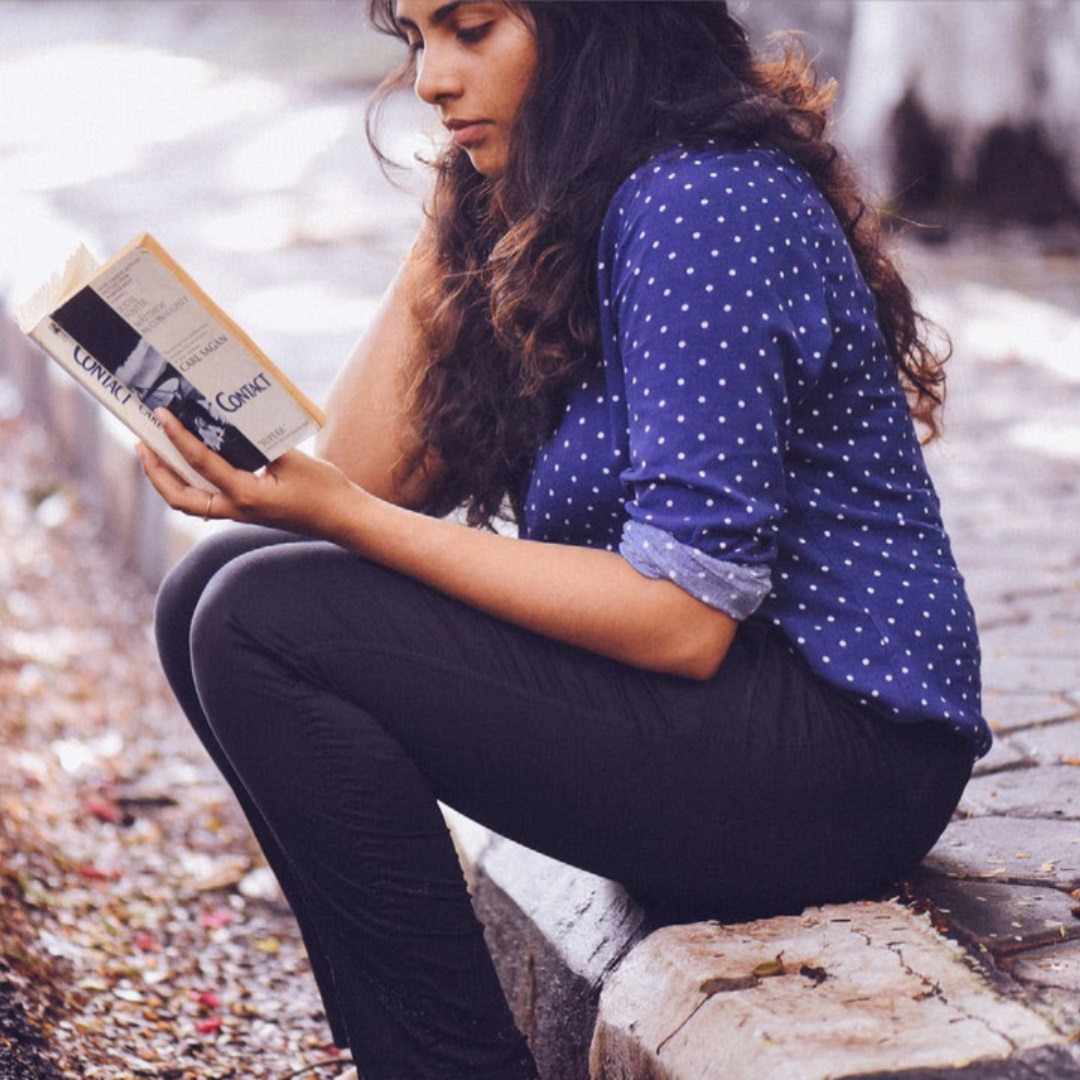Image of a young person sitting on the sidewalk and reading Contact.