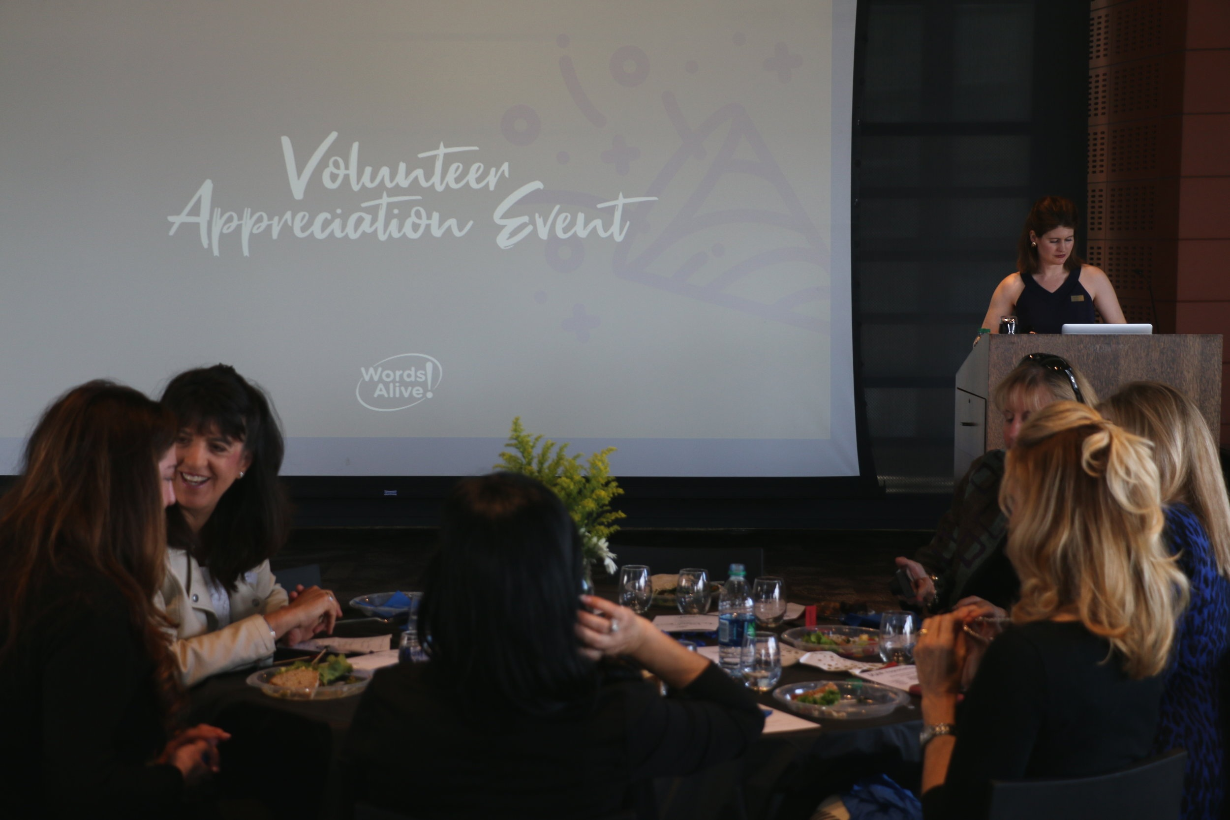 "An image of our Volunteer Appreciation Event. Volunteer Program Manager, Christina Meeker, stands at the podium in front of a screen that says ""Volunteer Appreciation Event."" Volunteers mingling over lunch also appear in the image."