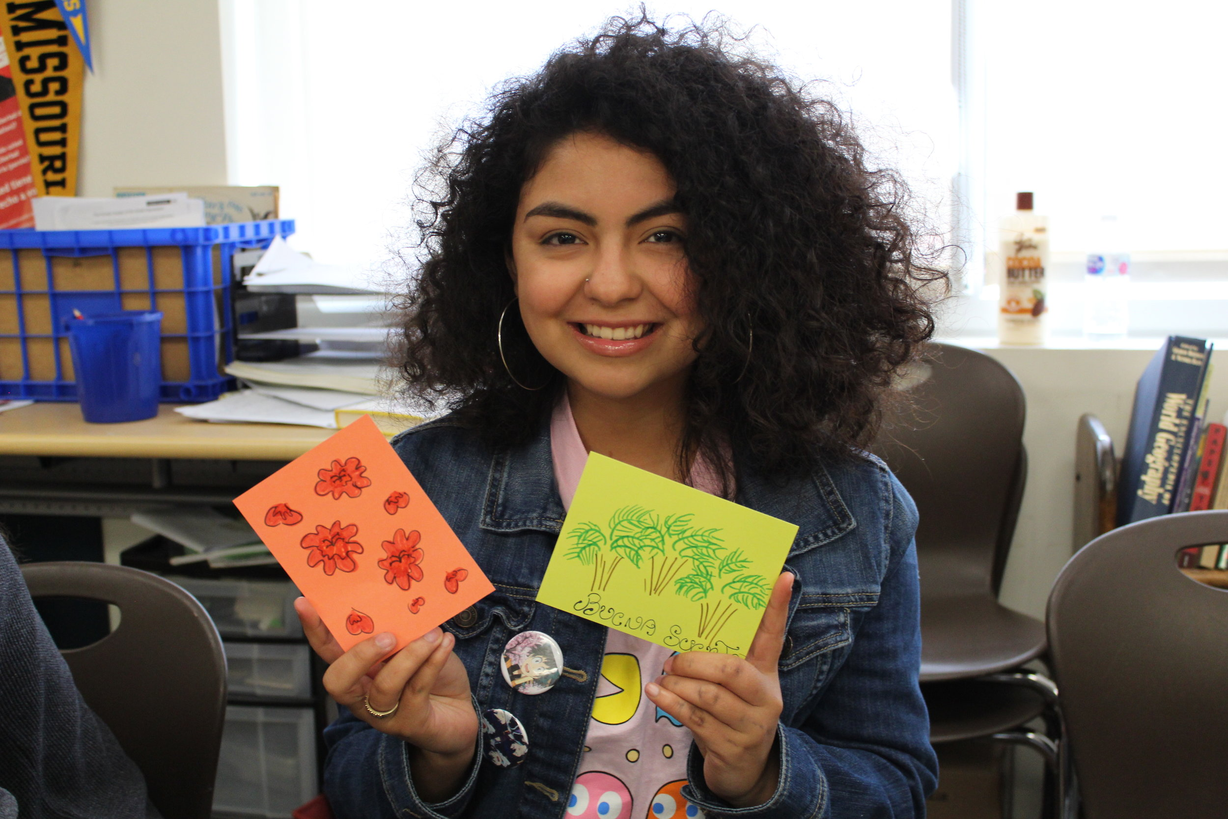 Image of a student holding up the welcome cards she wrote to asylum seekers.
