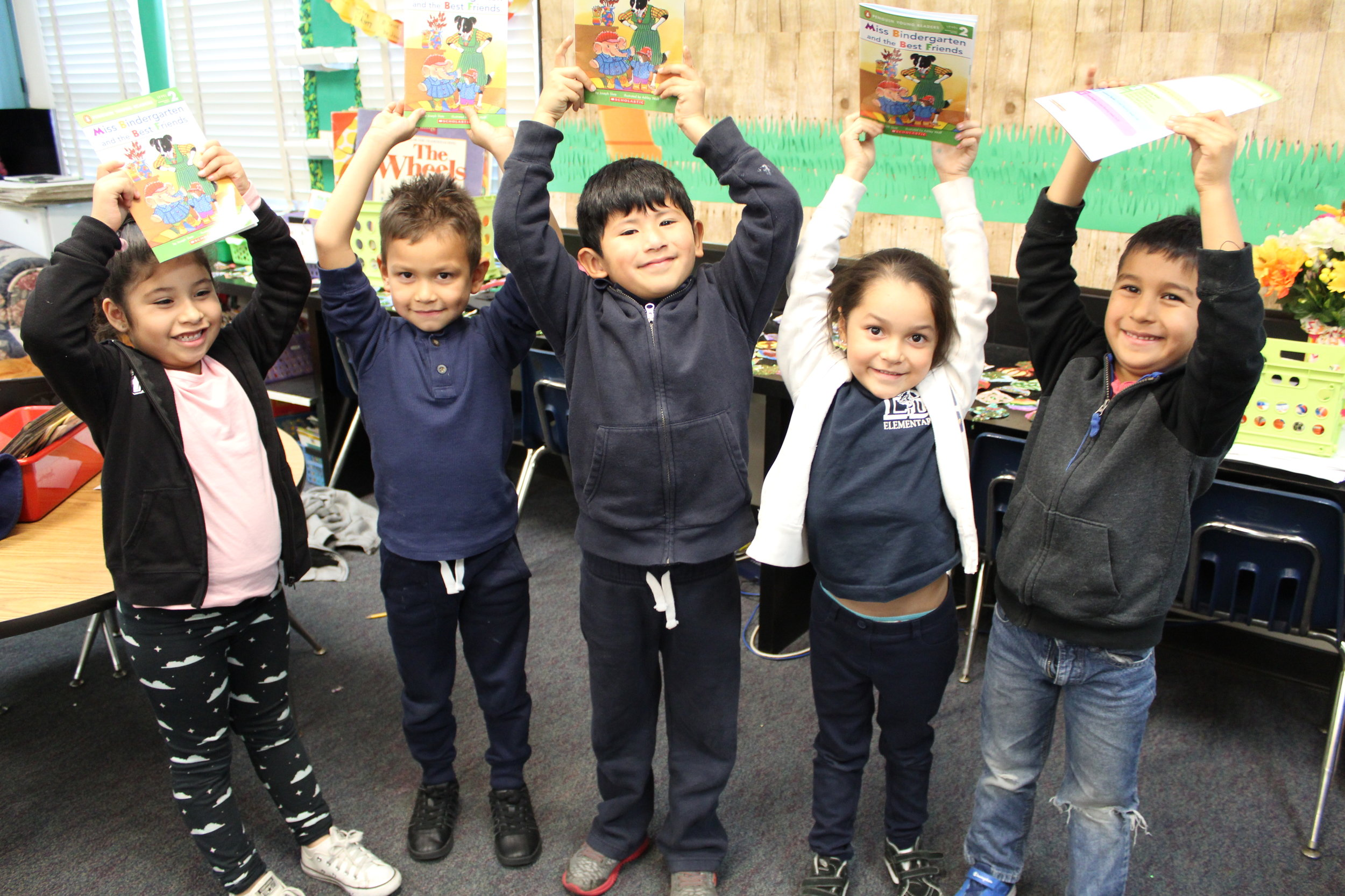 An image of five of our Read Aloud participants excitedly holding up their new books!