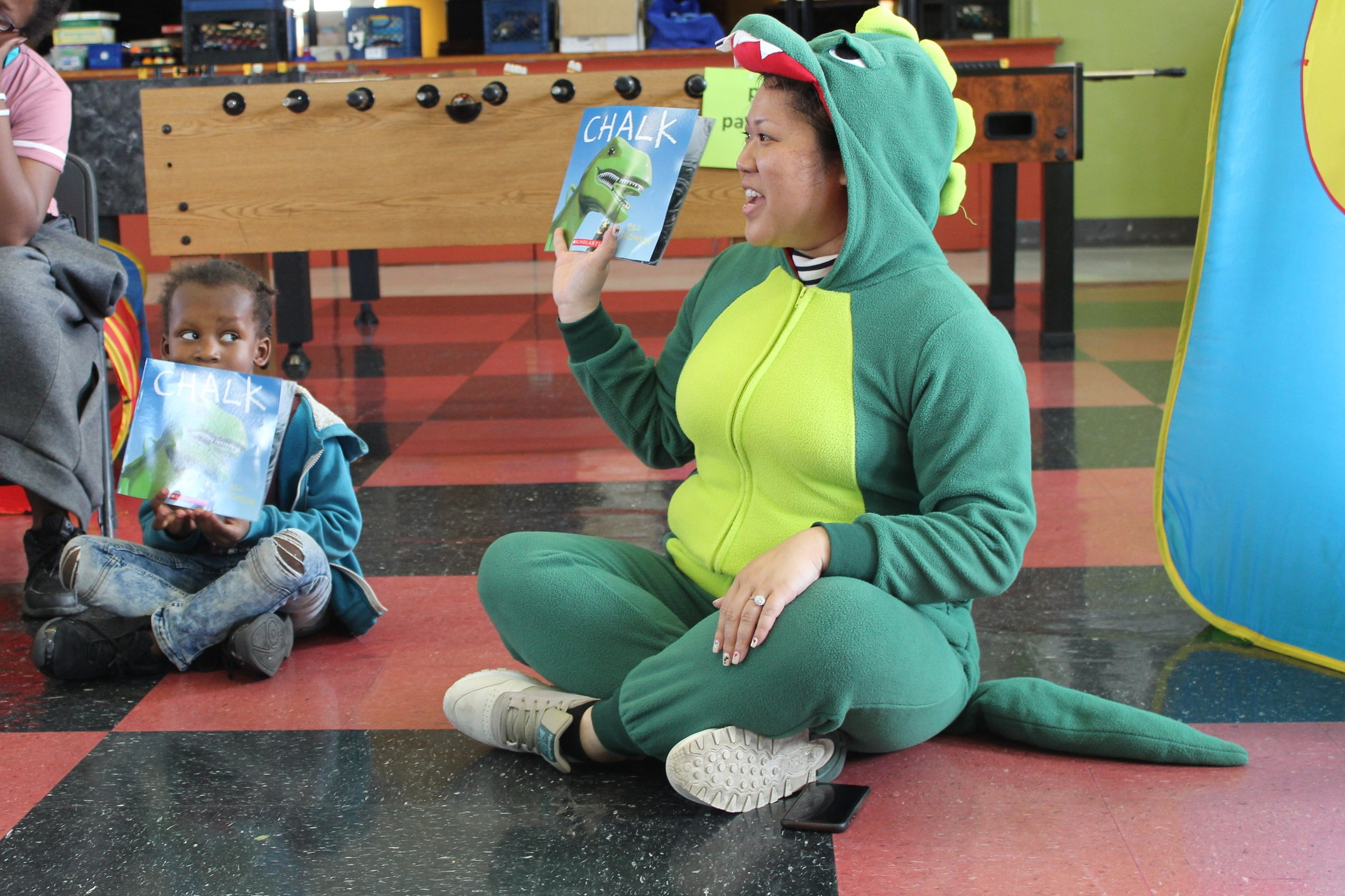 An image of Vichittra faciliting suring a Family Literacy Program session. She is wearing a dinosaur costume and holding up a book.