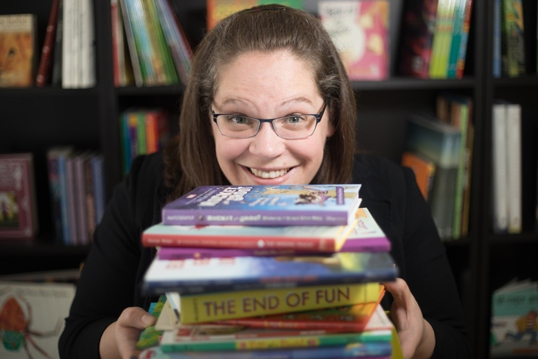 An image of Rachael looking at the camera and smiling while she holds a stack of books!