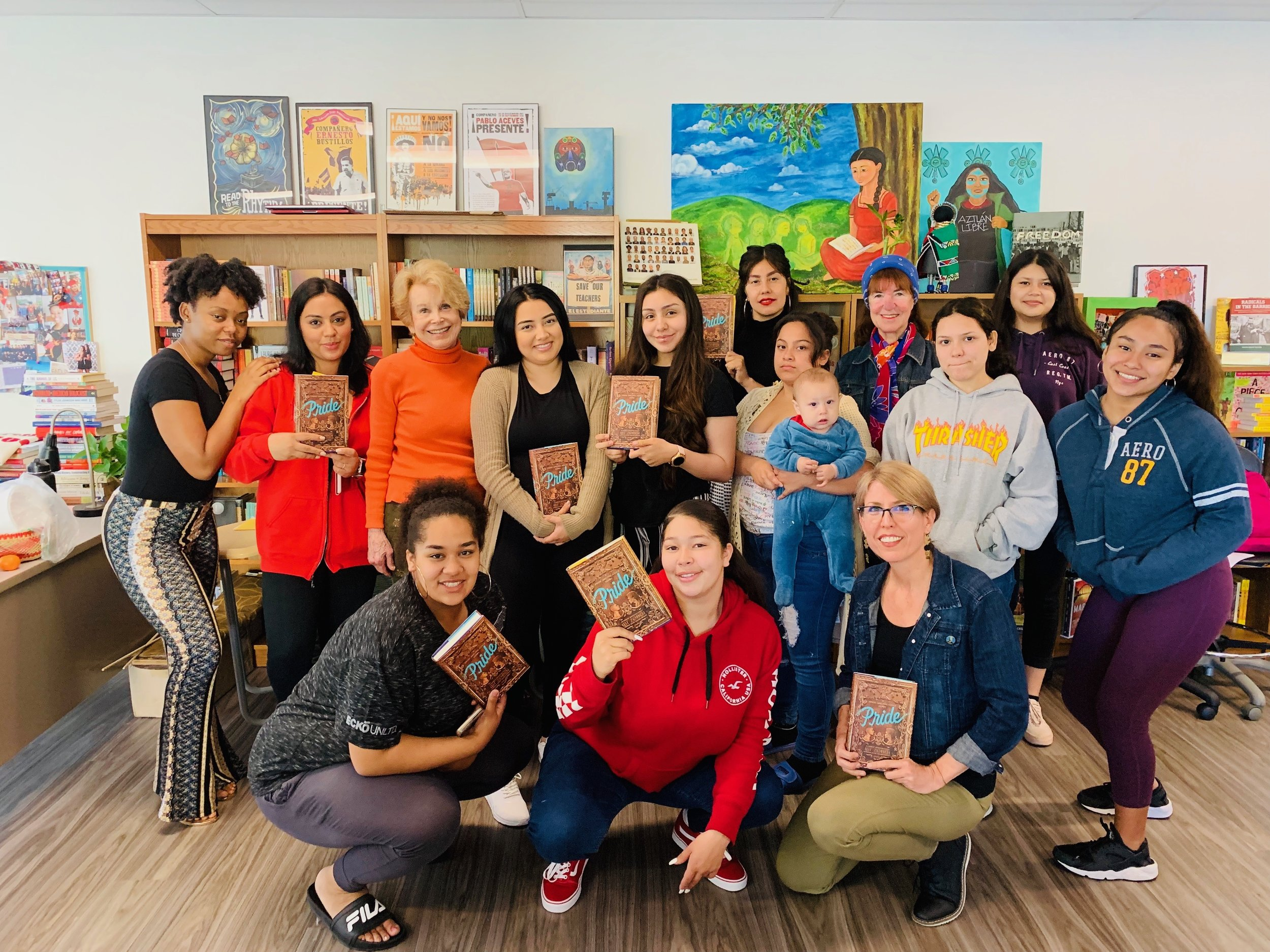 An image of Dawn with her students as they hold up copies of the book,  Pride .