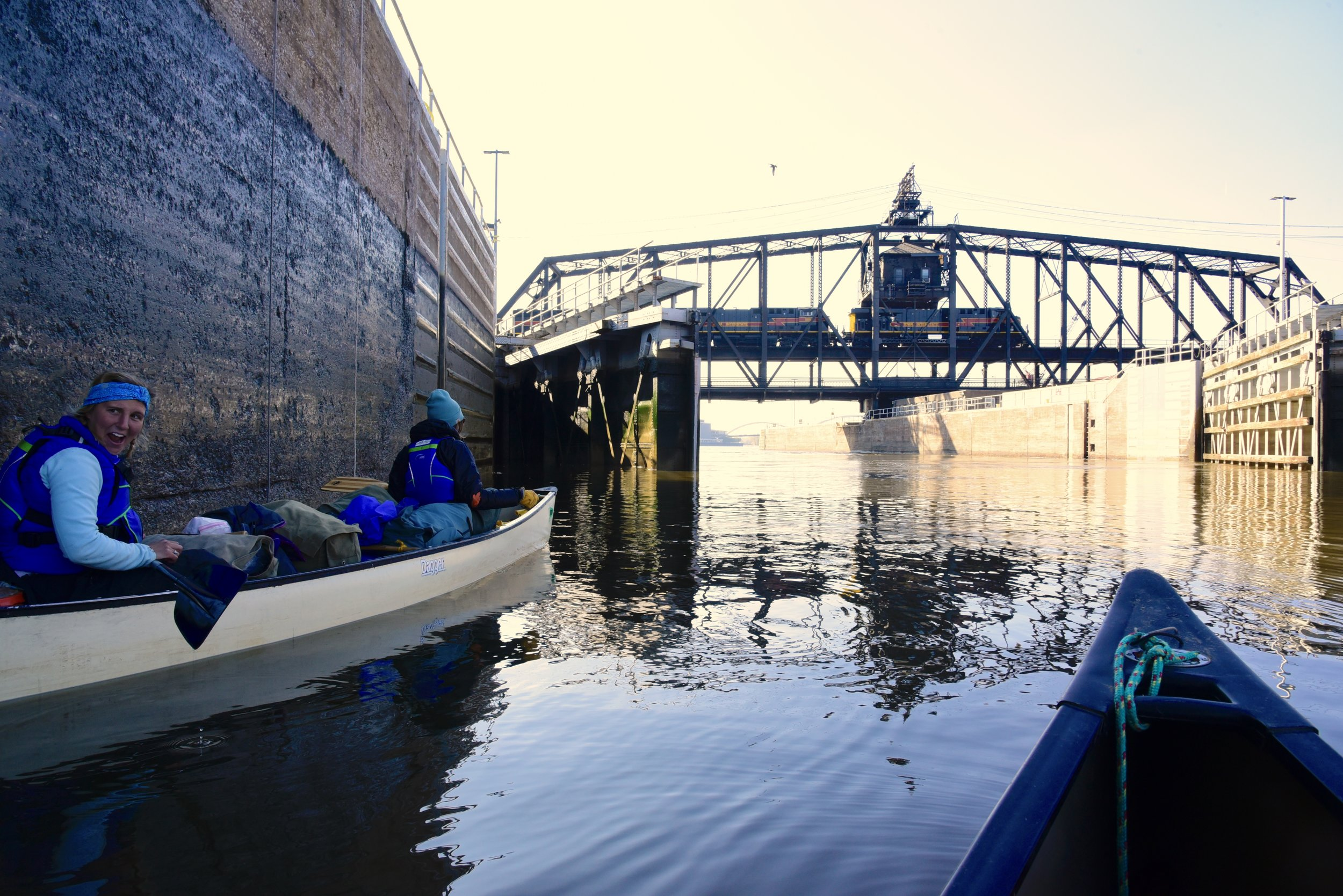 Grace Werner, left, and Mandy Hoffmeister wait to pass through Lock and Dam 15 on the Mississippi River as a train passes overhead. Werner and Hoffmeister, along with Siri Berg-Moberg and Grace Heneghan, paddled 1,800 miles of the Mississippi in the fall of 2017. Together they raised awareness and $3,500 for the YMCA program,  Girls Outdoor Leadership Development , a program that gets underrepresented youth outside to gain wilderness skills and confidence.