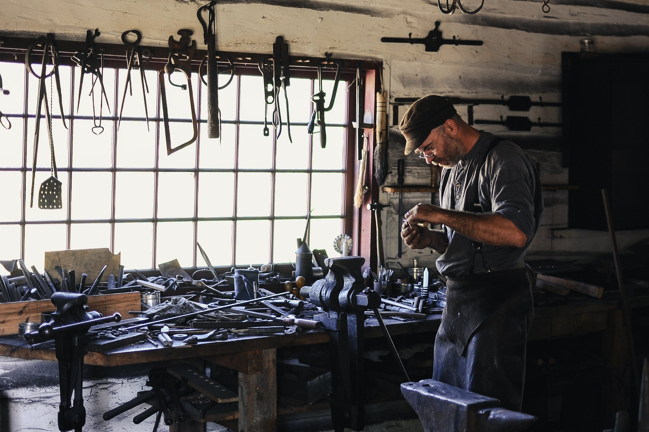 In this image, a craftsman engages in a blacksmithing task in his cluttered workshop. Craftsmen and artisans have always known that tools and resources are essential to their ability to produce. If a blacksmith lacks the right hammer, lacks sufficient time, or otherwise doesn't have what he needs, there's no way he or she can shoe a horse.  Photo courtsey of  Clark Young  on  Unsplash .