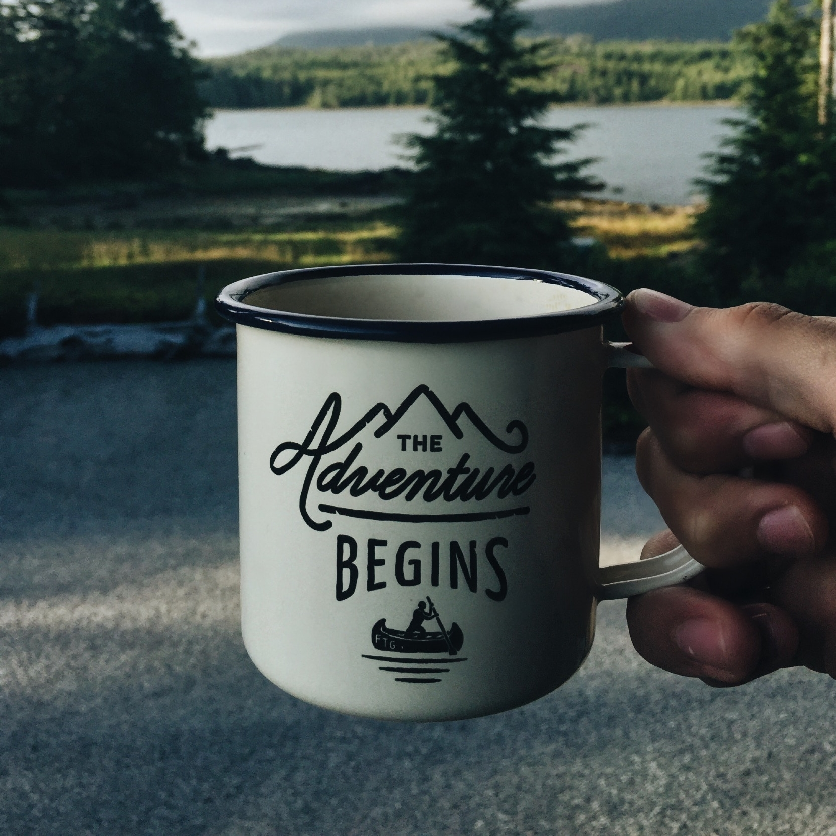 """When building any kind of a custom system, I'm reminded of waking-up early before a long trip and enjoying a cup of coffee. Just as the caption on this coffee cup set against the backdrop of trees and a lake suggests, """"The adventure begins,"""" when you commission a custom LMS so make sure to fuel-up on caffeine!  Photo courtesy of  Matthew Sleeper on  Unsplash"""