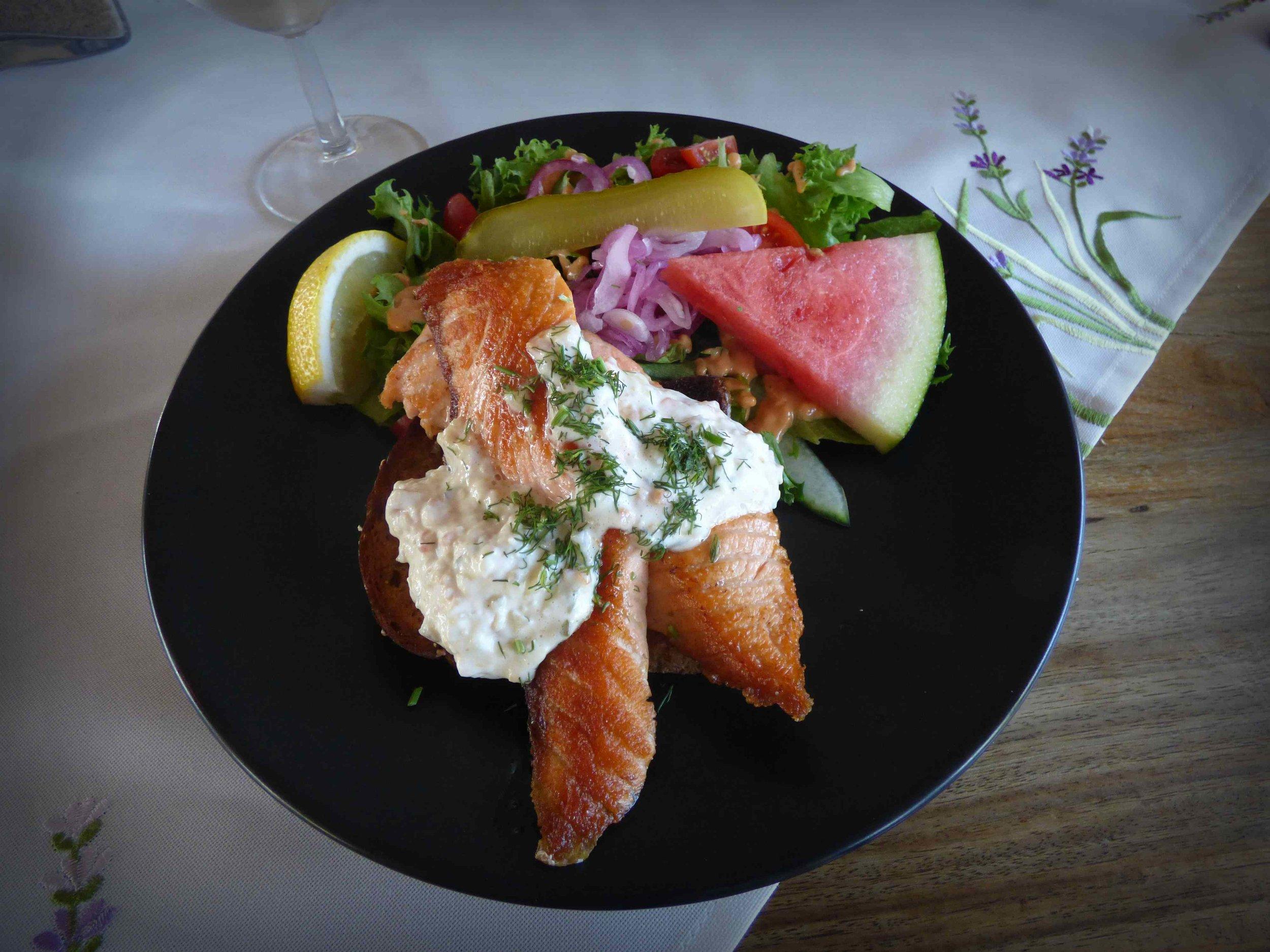 Lautasella päivän teemaan sopien; Harrbådan lohileipä tartarkastikkeella ja salaatilla