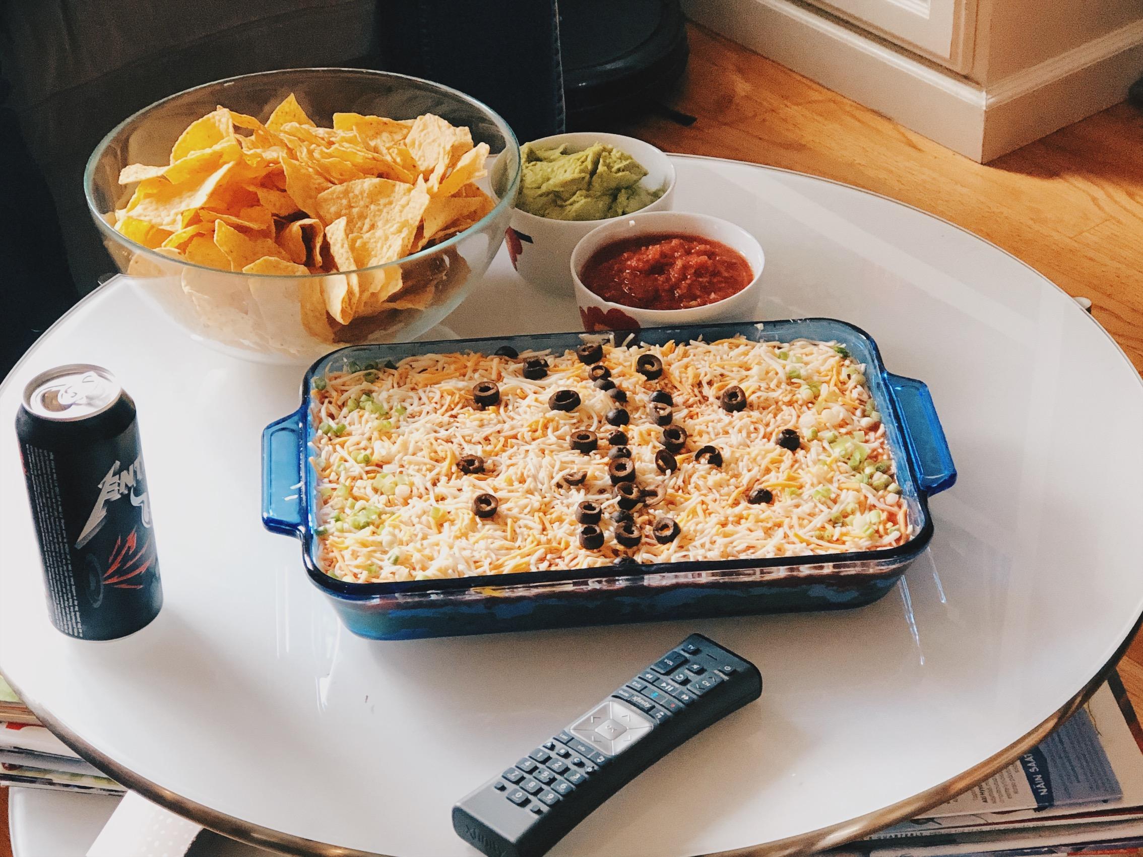 7 layer dip; refried beans, guacamole, salsa, kermaviili, juustoraaste, oliivit, kevätsipuli