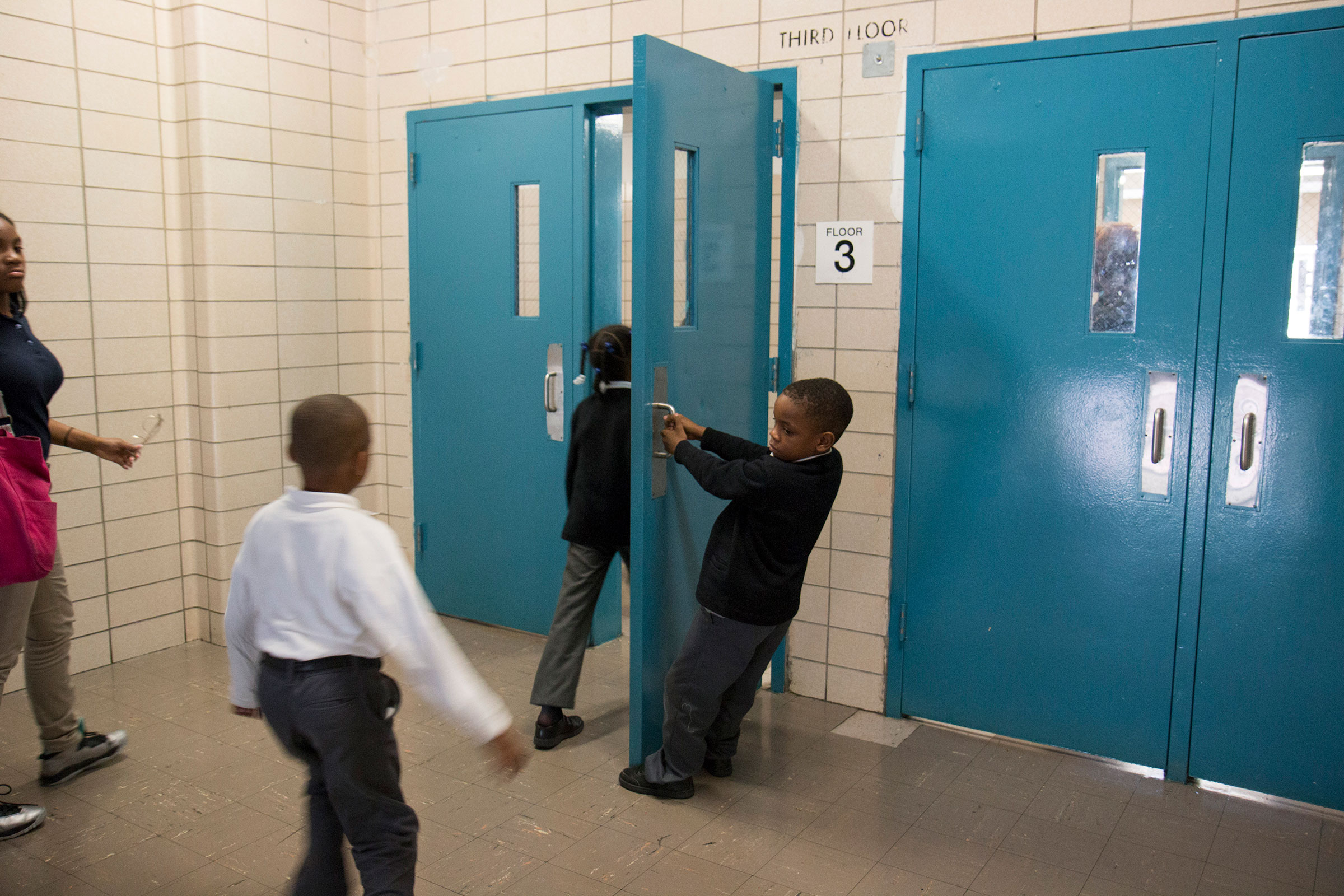 Second grader, Aiden, opens the door to the hall for fellow students and teachers at Leadership Prep Canarsie in Brooklyn, NY.