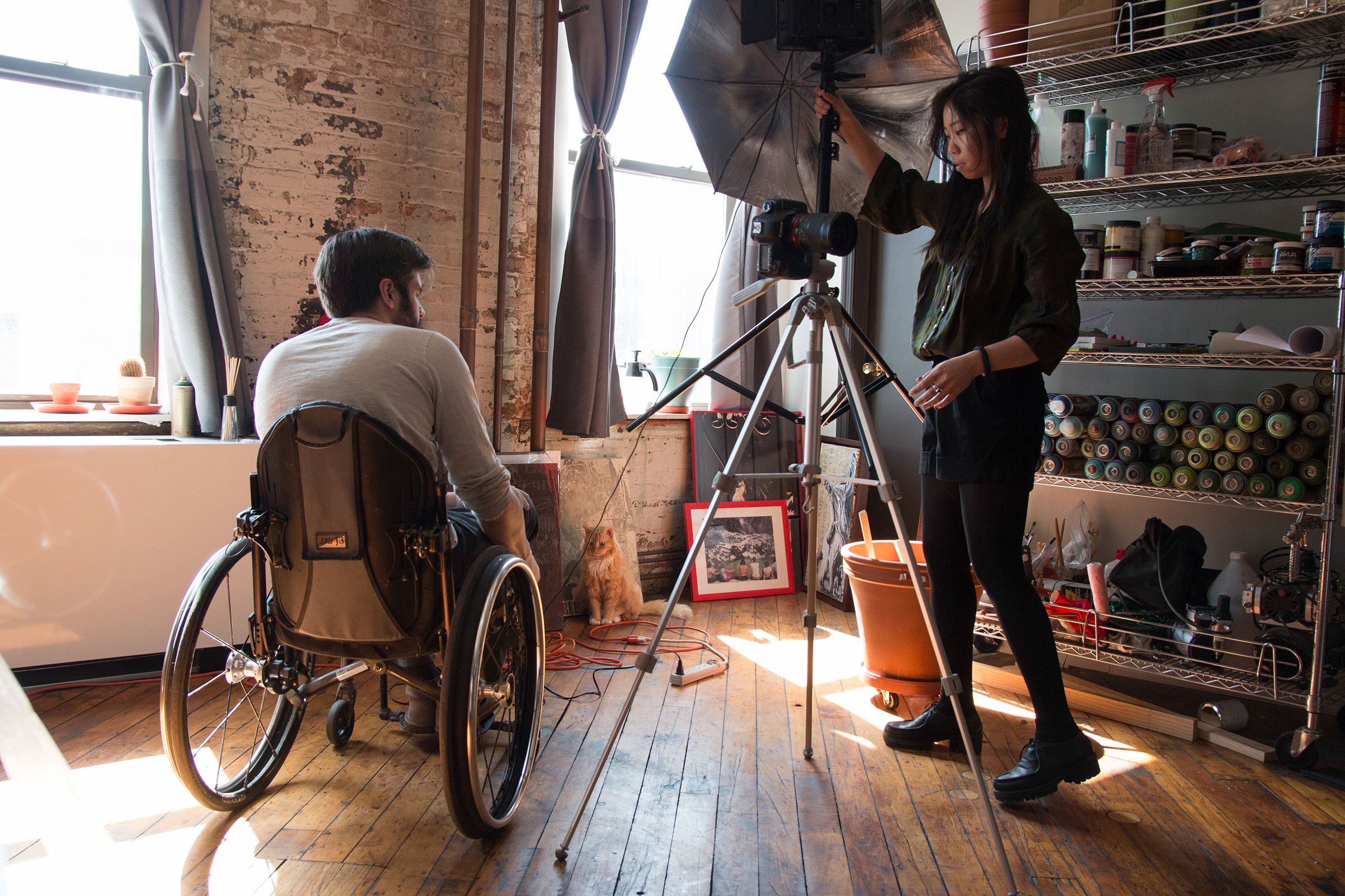 Filmmaker Chloe Lee modeled for many of B.D. White's stencils and paintings. She helps White take photographs of the work at his studio.