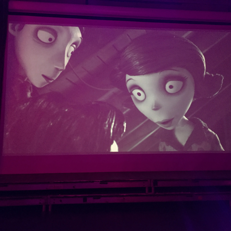 Clips from classic Tim Burton films play on a large screen at the front behind the stage.