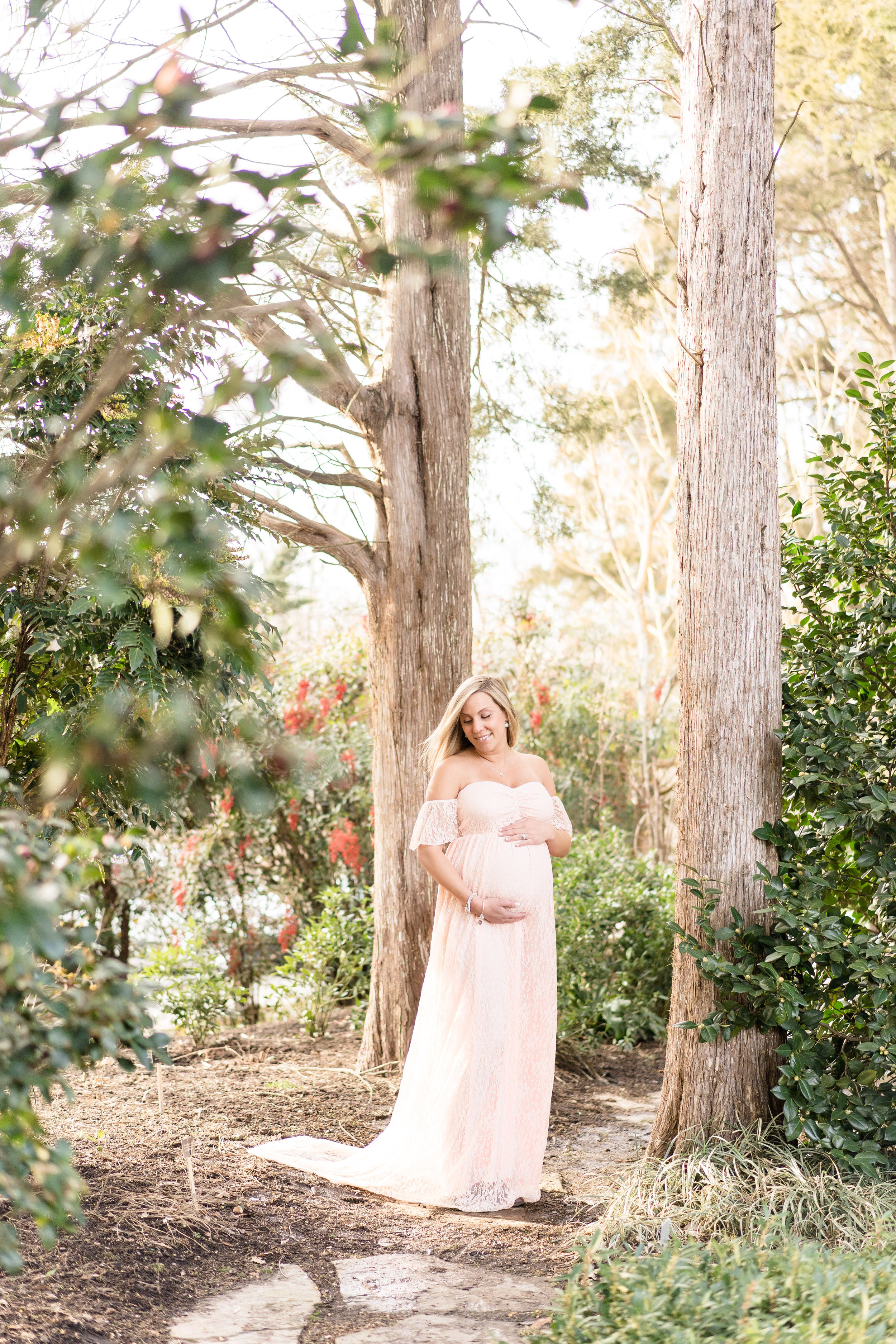 Top northern virginia maternity photographer near me captures stunning Mom pregnant with her baby girl in gorgeous pale pink maternity gown in stunning greenery.
