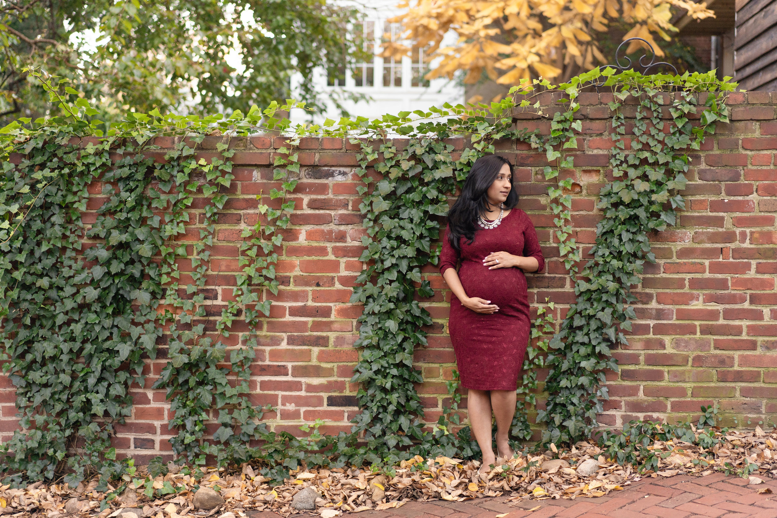 Best Loudoun county photographer, katy hayes, captures a stunning mom to be against a brick wall in old town Alexandria during her maternity session