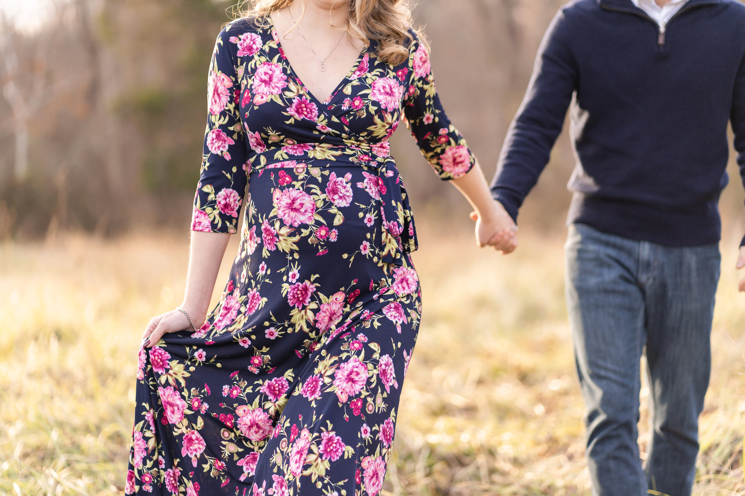 mom and dad to be hold hands during their maternity session in Loudoun county by the best photographer
