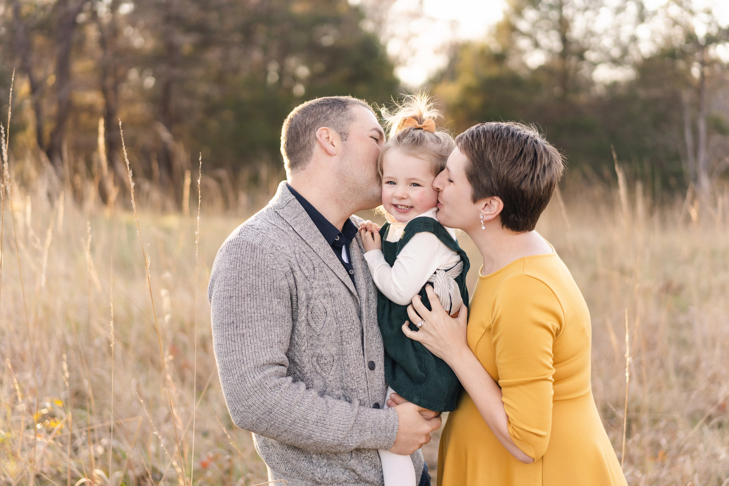 Mom and Dad kiss their little girl while expecting their second little girl. These magical moments captured by the best maternity photographer near me in northern virginia