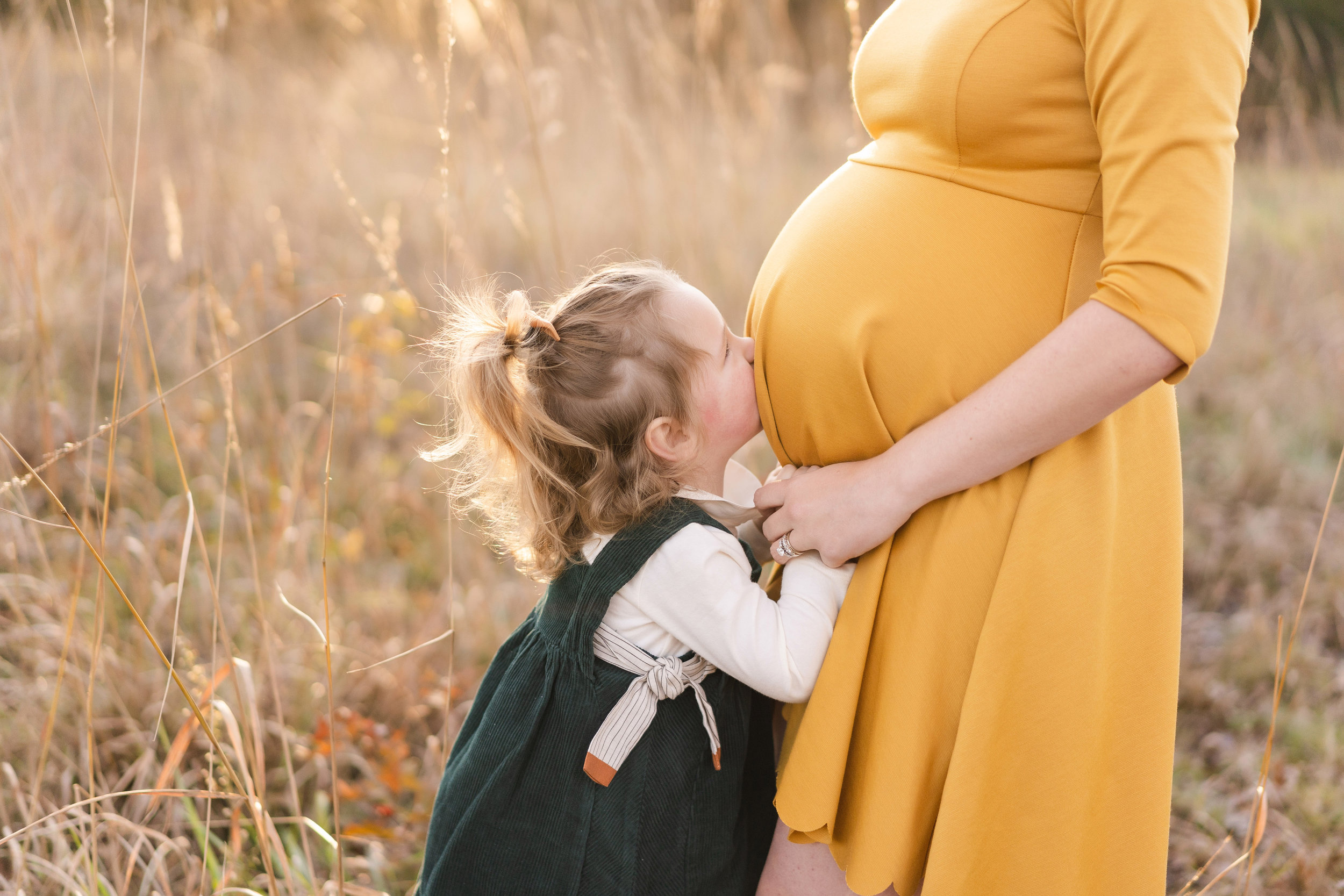 Adorable big sister kisses Moms belly during a maternity photo shoot at Manassas Battlefield by the best maternity photographer near me