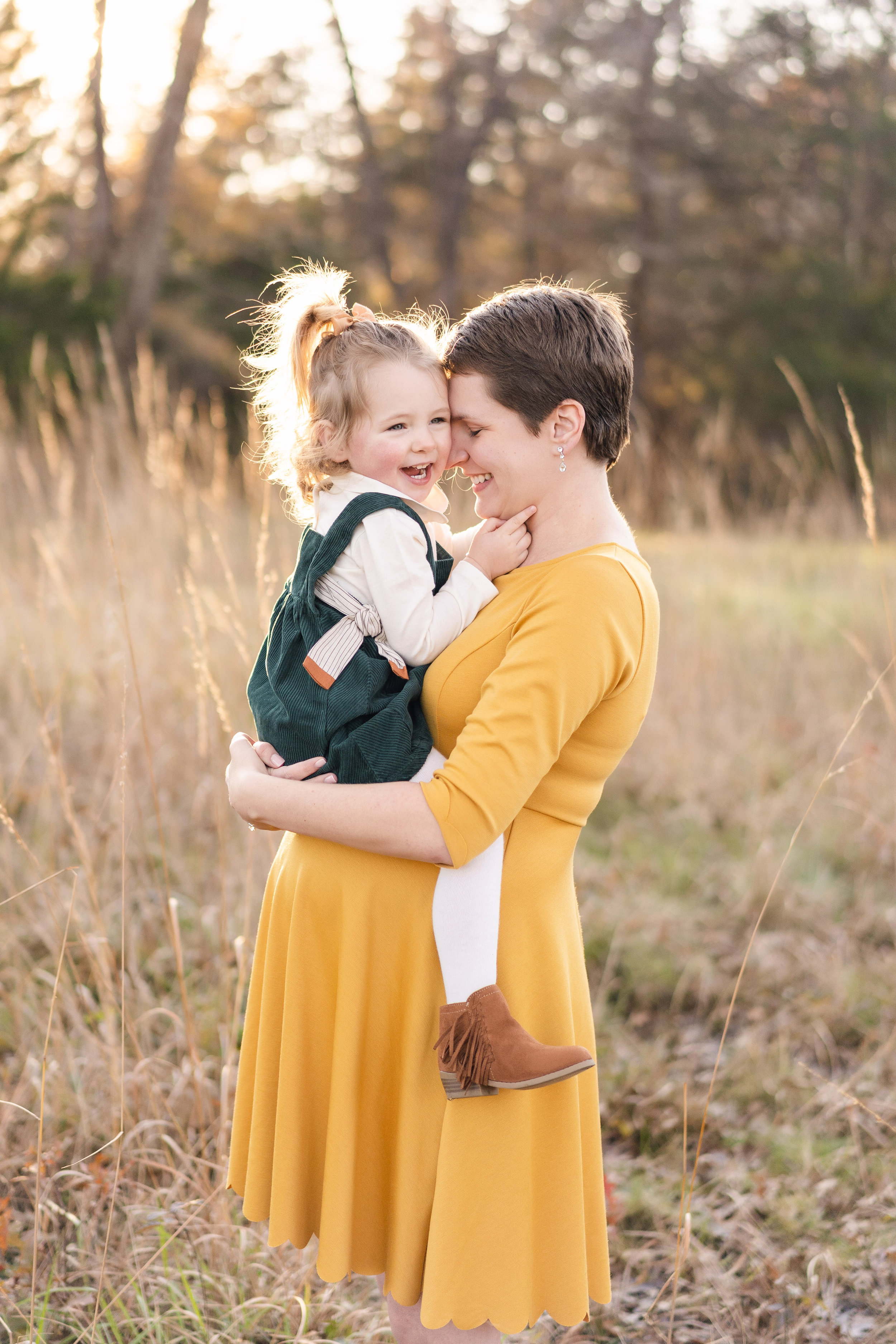 Big sister is held by her pregnant Mom during their maternity session. They are covered by the golden sunset in tall grass near me