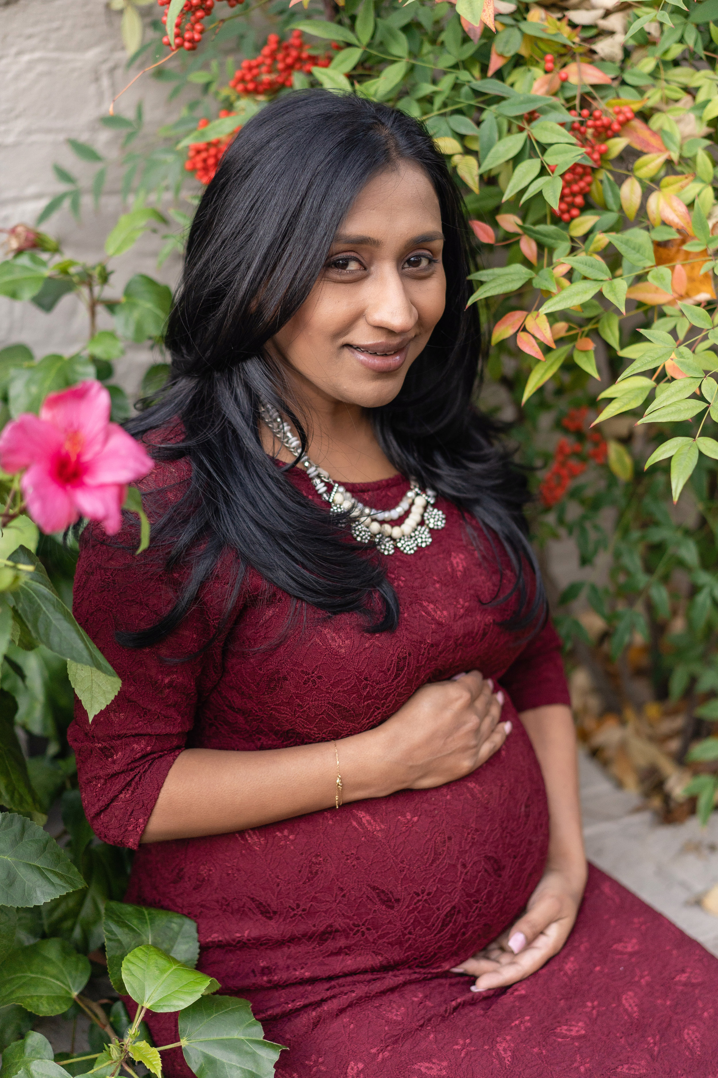 Mom hugs her belly and sits in a gorgeous display of flowers for her maternity session in Washington DC