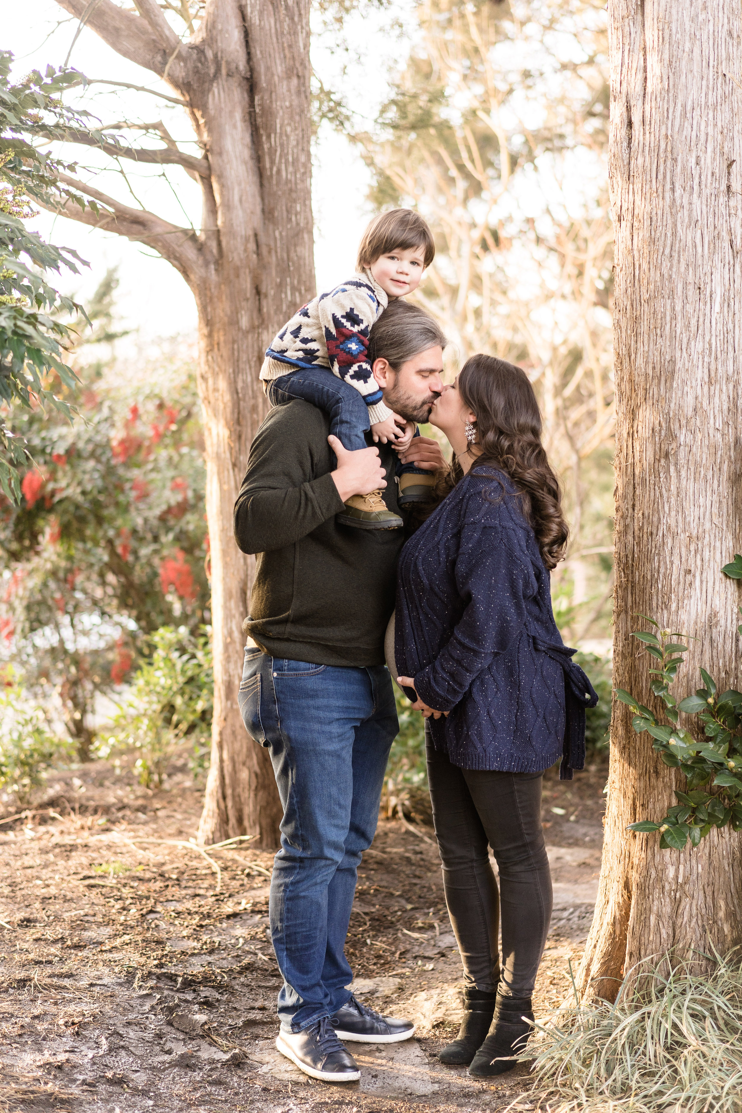 Happy couple kiss during their maternity session at Green Springs Garden with Northern Virginia photographer, Katy Hayes