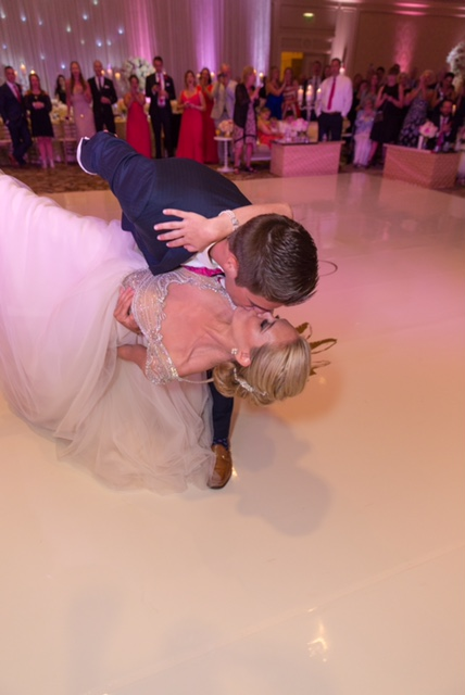 Husband and wife dip and kiss during their first dance