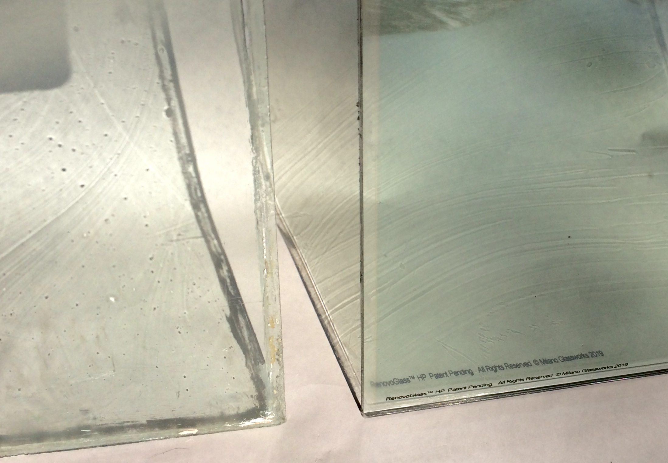 RenovoGlass™ HP (High Performance). This example illustrates a custom high performance restoration glass next to an original C1870 historic glass. Using natural light to project the subtle surface striation allows you to see exactly the nuance of our progressive historic glass products. The historic glass has many pits from over 140 years of exposure to the elements.