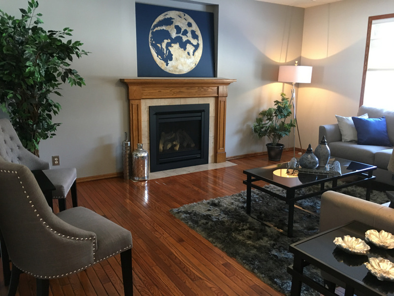 The living room looks lighter with fresh colour, and the fireplace is highlighted on the accent wall with artwork. The room looks warm, bright and inviting now.