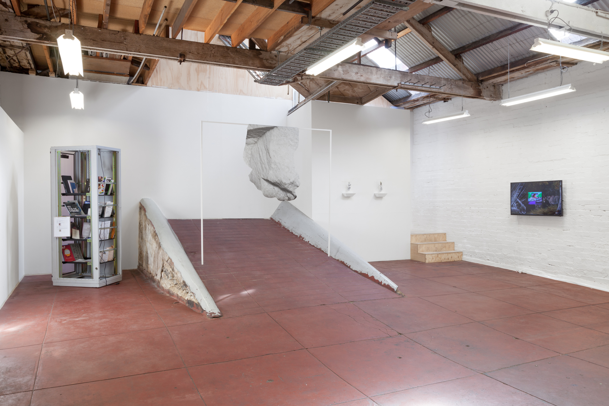 Tabularium installation view, Slopes, 2014.  Left: Alana Kushnir, Tabularium Archive, 2014 – ongoing, publications with an online ethos unavailable in digital form, server rack. Centre: Rachel de Joode, Hanging Marble, 2014, digital print on vinyl, MDF. Right: Katja Novitskova, Shapeshifter X, 2013 (left) and Shapeshifter V, 2013 (right), broken silicon wafers, epoxy clay, nail polish, appropriated acrylic case, appropriated wooden capital. Far right: Jon Rafman, Annals of Time Lost, 2013 (image still), single channel HD video, 6m 52s. Photograph: Christo Crocker.