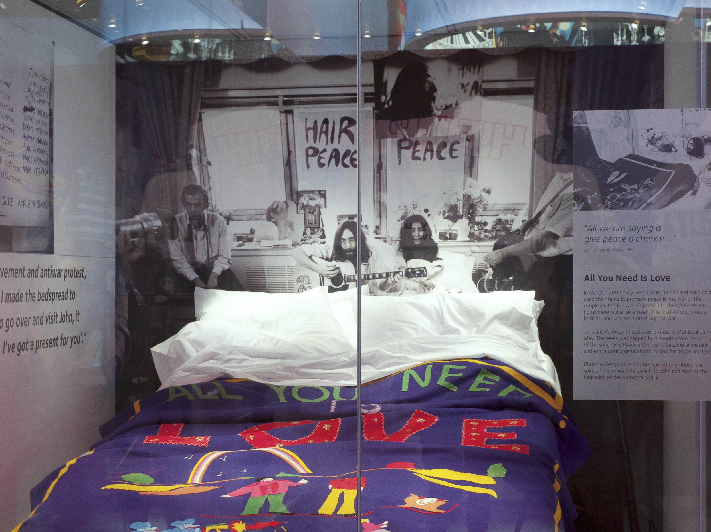 A glass display at the Museum of Liverpool containing John Lennon and Yoko Ono's 1969 peace protest bedspread, lit by Sutton Vane Associates.