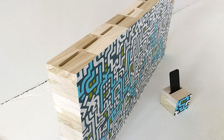 Complete wall of wooden blocks with Separate wooden block with cell phone in slot - Mr. Upside Gallery Voorburg - Artwork Dutch contemporary artist Mr. Upside Michiel Nagtegaal painting KPN Teamdag 2016 give-away gift kunst cadeau in Mr. Upside Studio