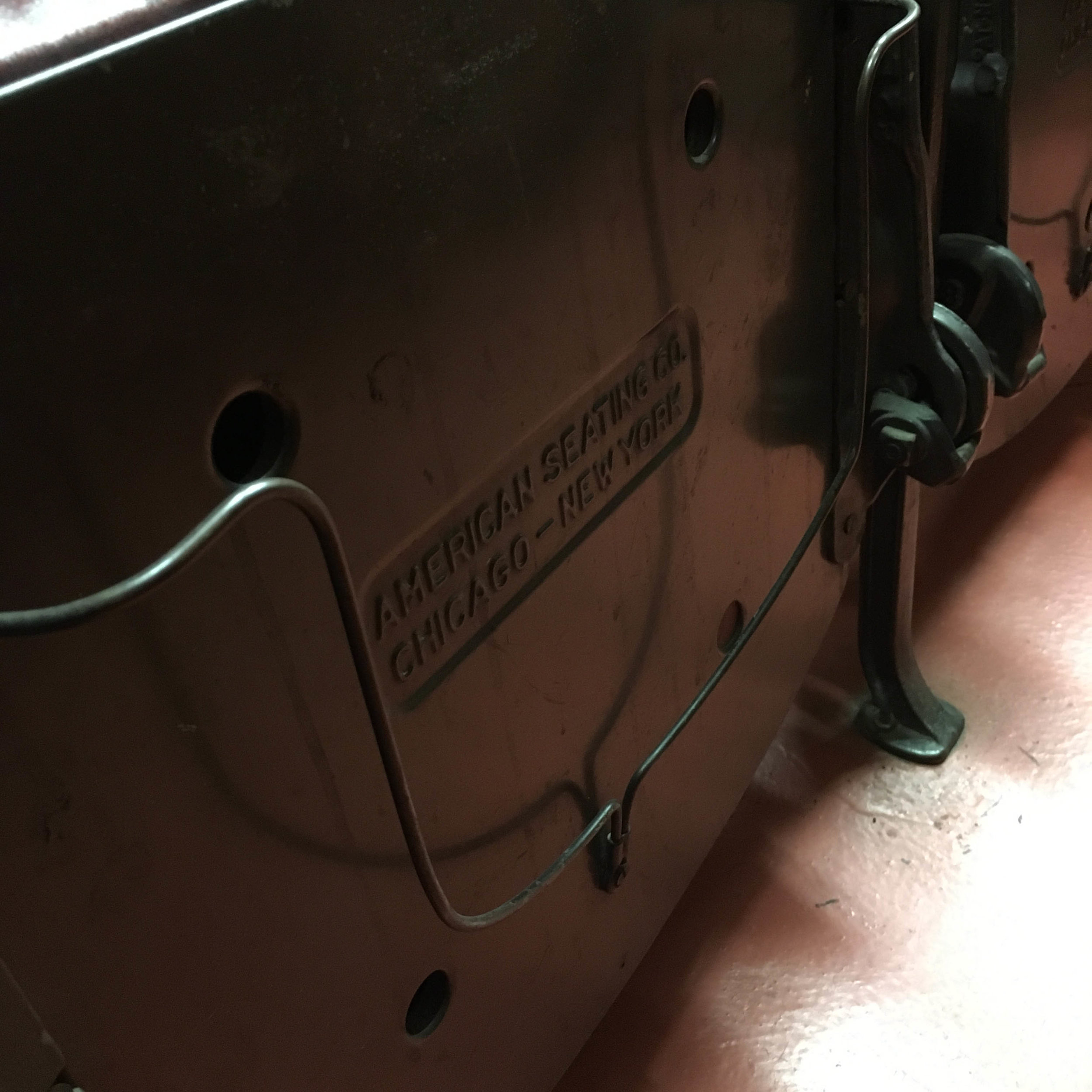 Bottom of the seats in the newsreel theatre, where passengers would come to catch the news while waiting for their trains.  Why is the bottom of the seat so interesting? This wire mechanism was used to hold passengers' hats while they waited.