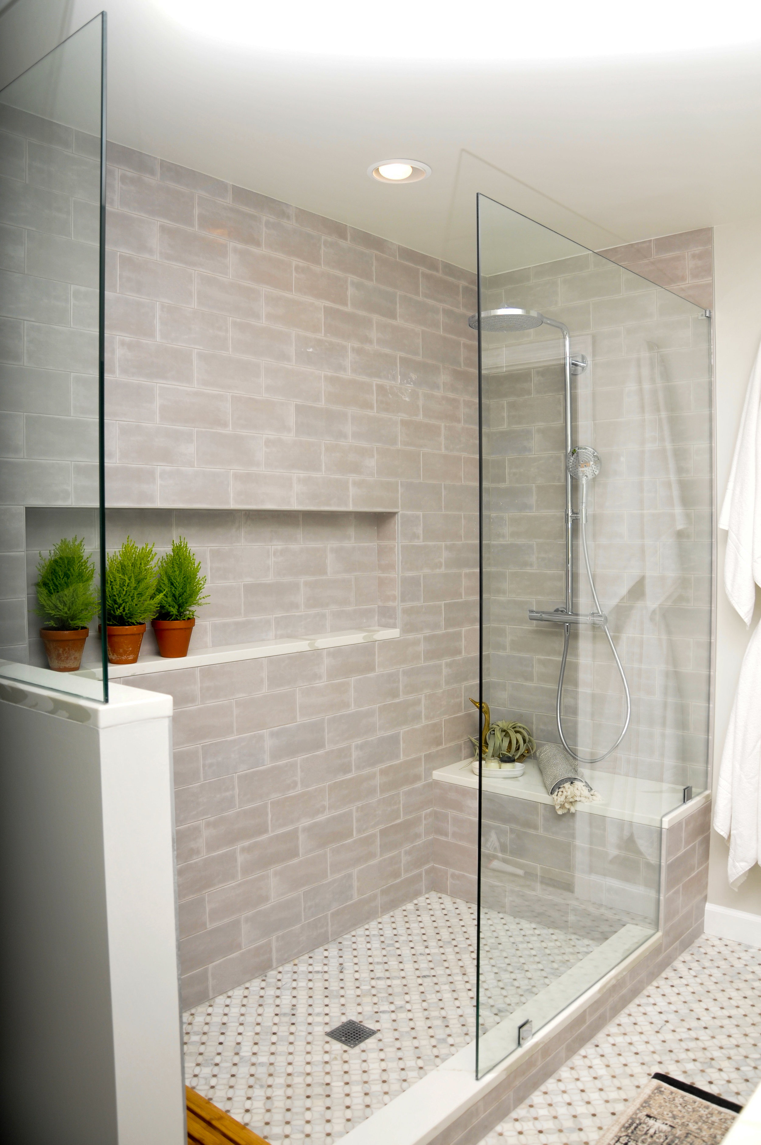 The large walk in shower has a European feel with partial glass enclosure and Hansgrohe fixtures. {Photograph by Brooke Mullins Photography}
