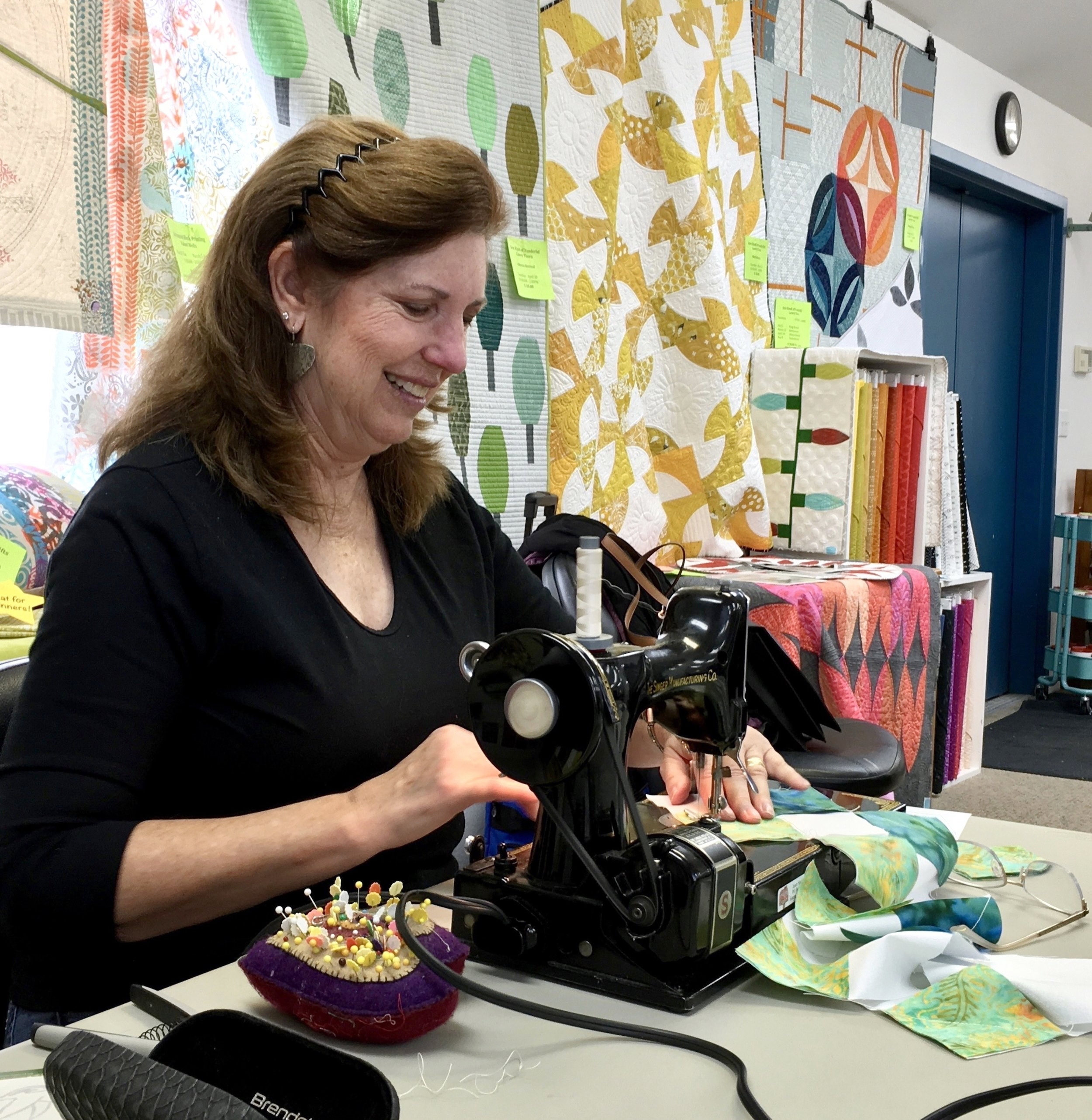 "East of the Cascades Quilters (EOCQ) member Janet Storton guides fabric through her vintage Singer Featherweight to prepare a blank square for the Sisters Country signature quilt. ""My love for quilting and this community drew me to the project,"" Storton says. Several EOCQ members have generously volunteered their time to help C4C bring the quilt to life.   All area residents are invited to join that effort by writing sentiments on quilt squares during Values & Visioning Days booths, set for March 9, 10, 16 and 17."