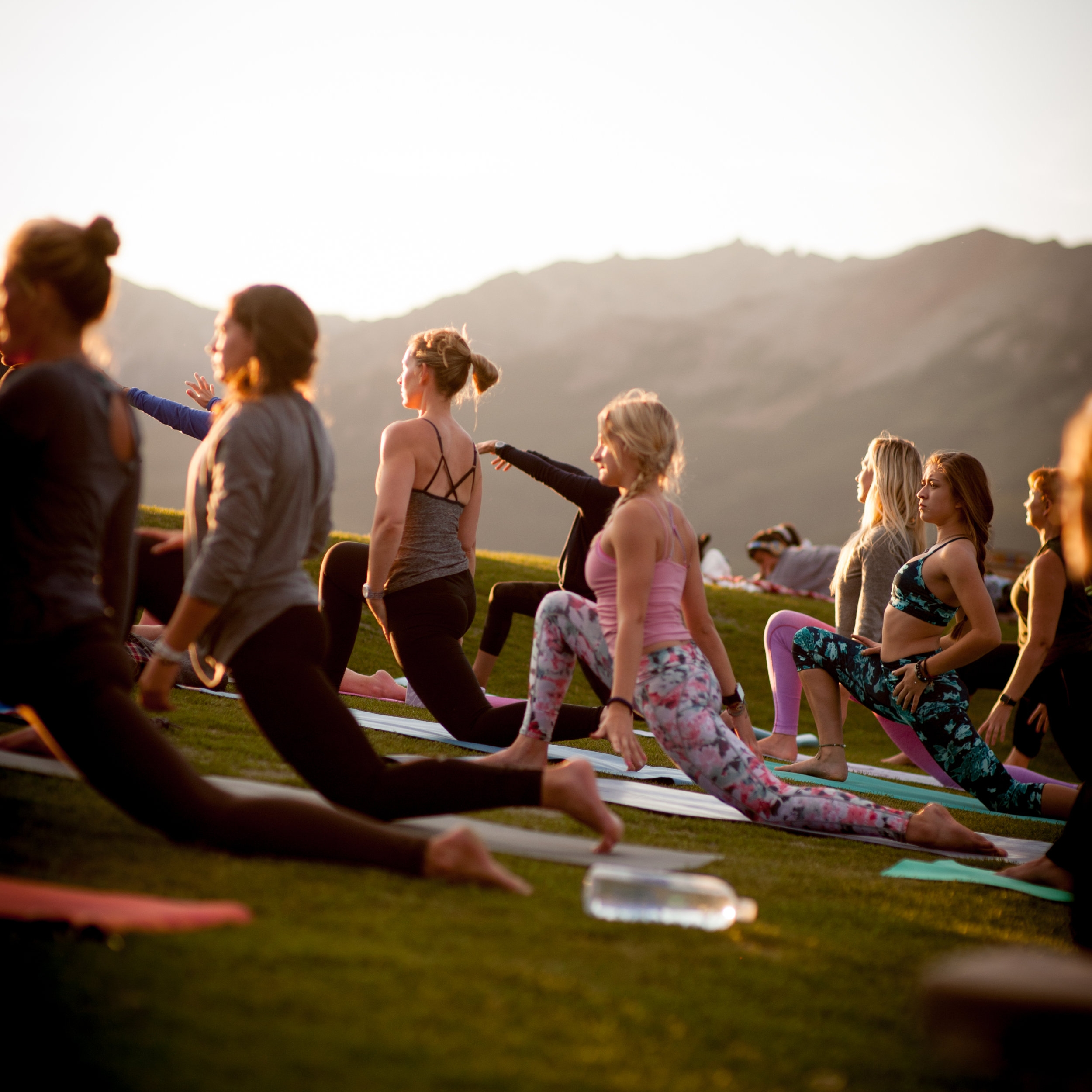 Yogis low-lunge under the sunset mountains.
