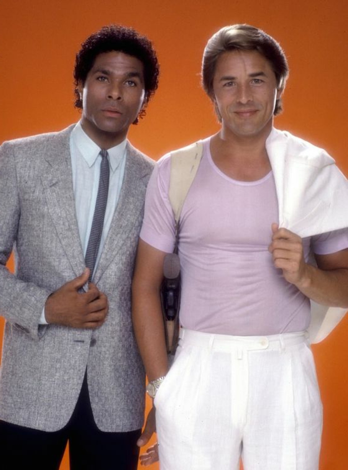80-s-fashion-for-men-two-men-african-american-with-suit-and-tie-black-trousers-caucasian-pink-tshirt-white-trousers-white-jacket-orange-background.jpg