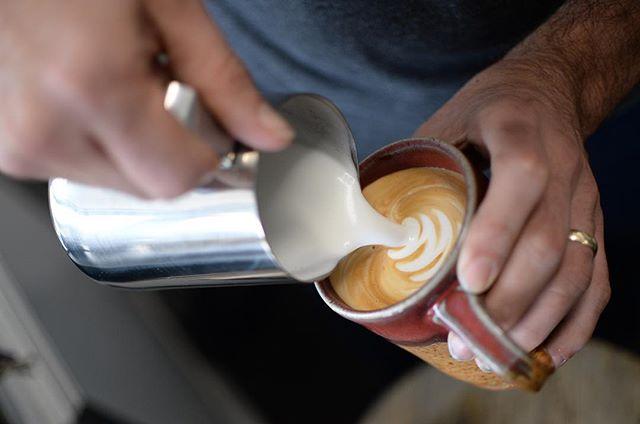 Pouring steamed milk into ceramic mug to make a latte