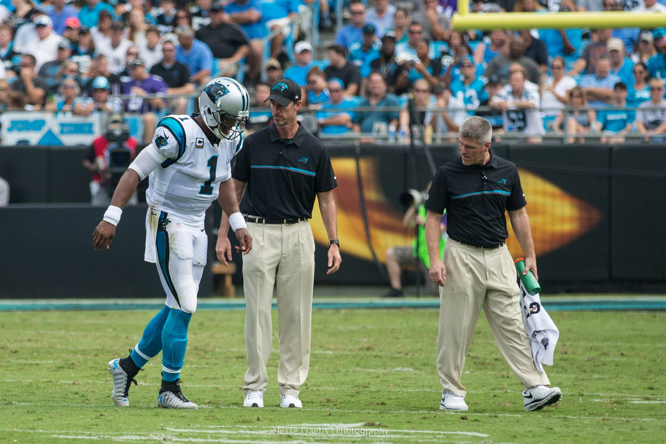 A limping Cam assisted off the field by doctors.