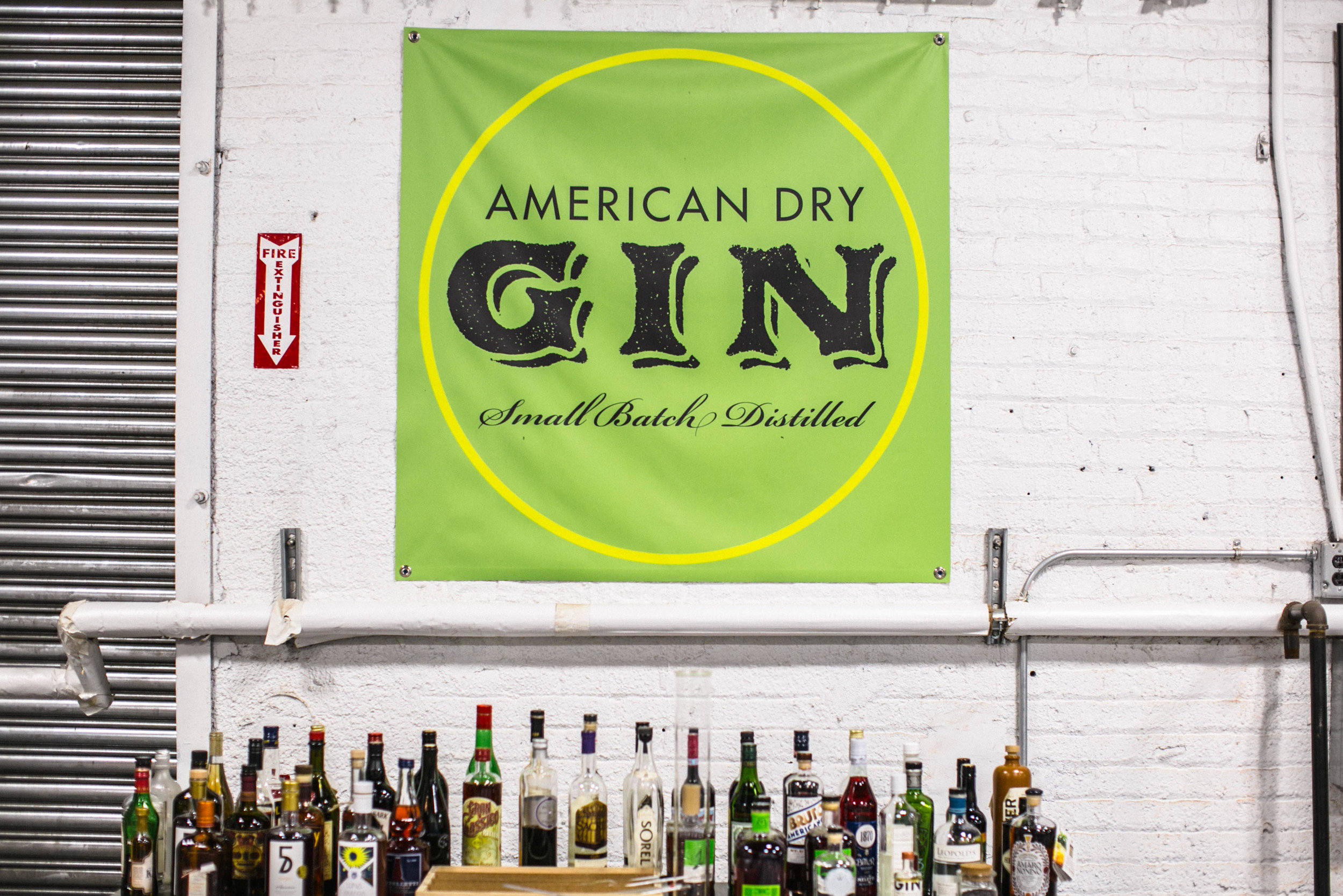 Signature bottles stand beneath the Greenhook Gin flag in the modest Greenpoint distillery.